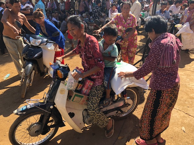 Recipients of donations from LDS Charities in Maha Leap load their goods onto motor bikes following the ceremony with the governor. The food donations were given directly to those in need in the community.