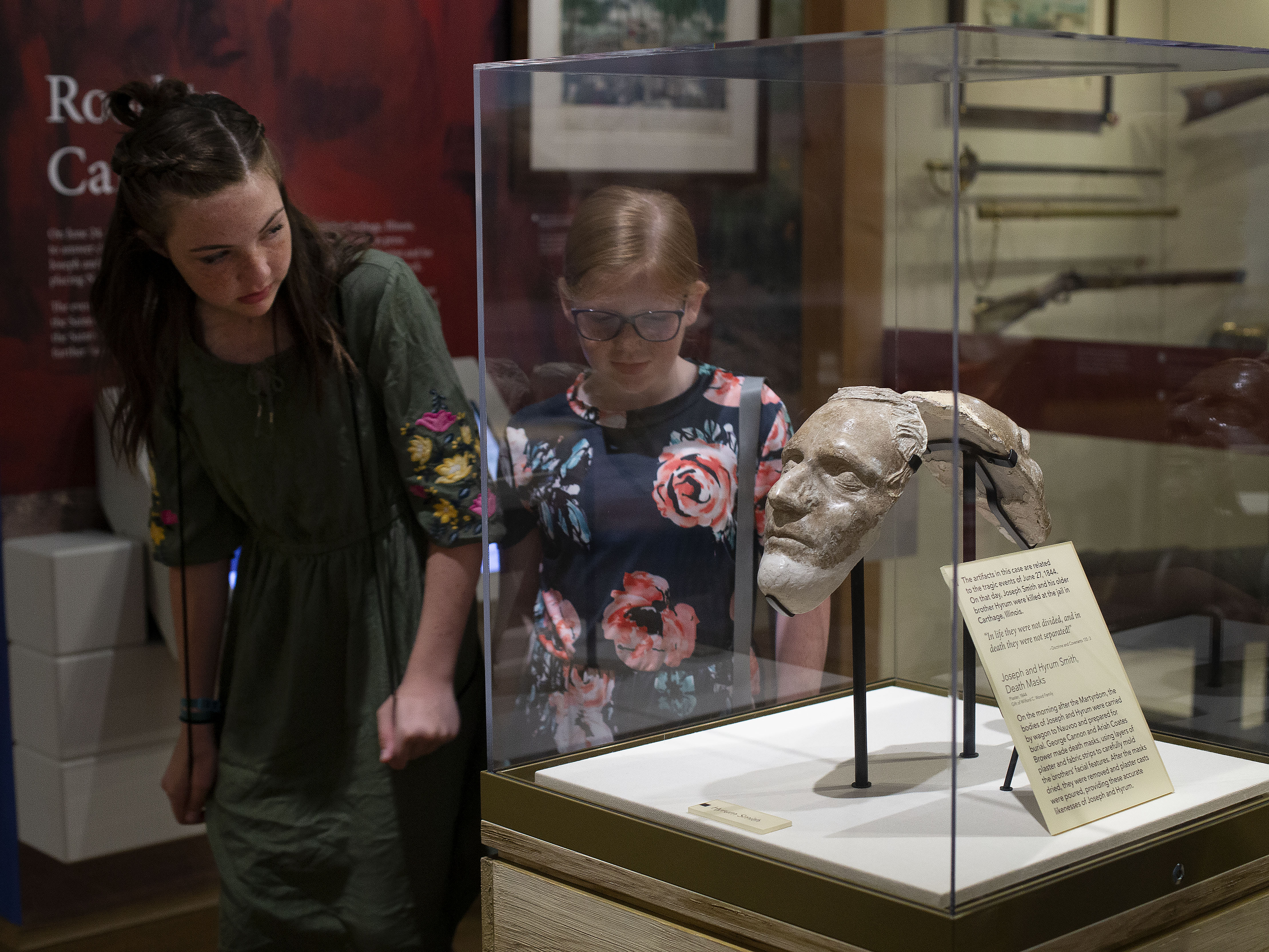 Brielle Fawson, 14, and Savannah Carter, 12, of Grantsville, look at the Dibble death masks of Hyrum and Joseph Smith at the Church History Museum in Salt Lake City on Thursday, June 13, 2019.