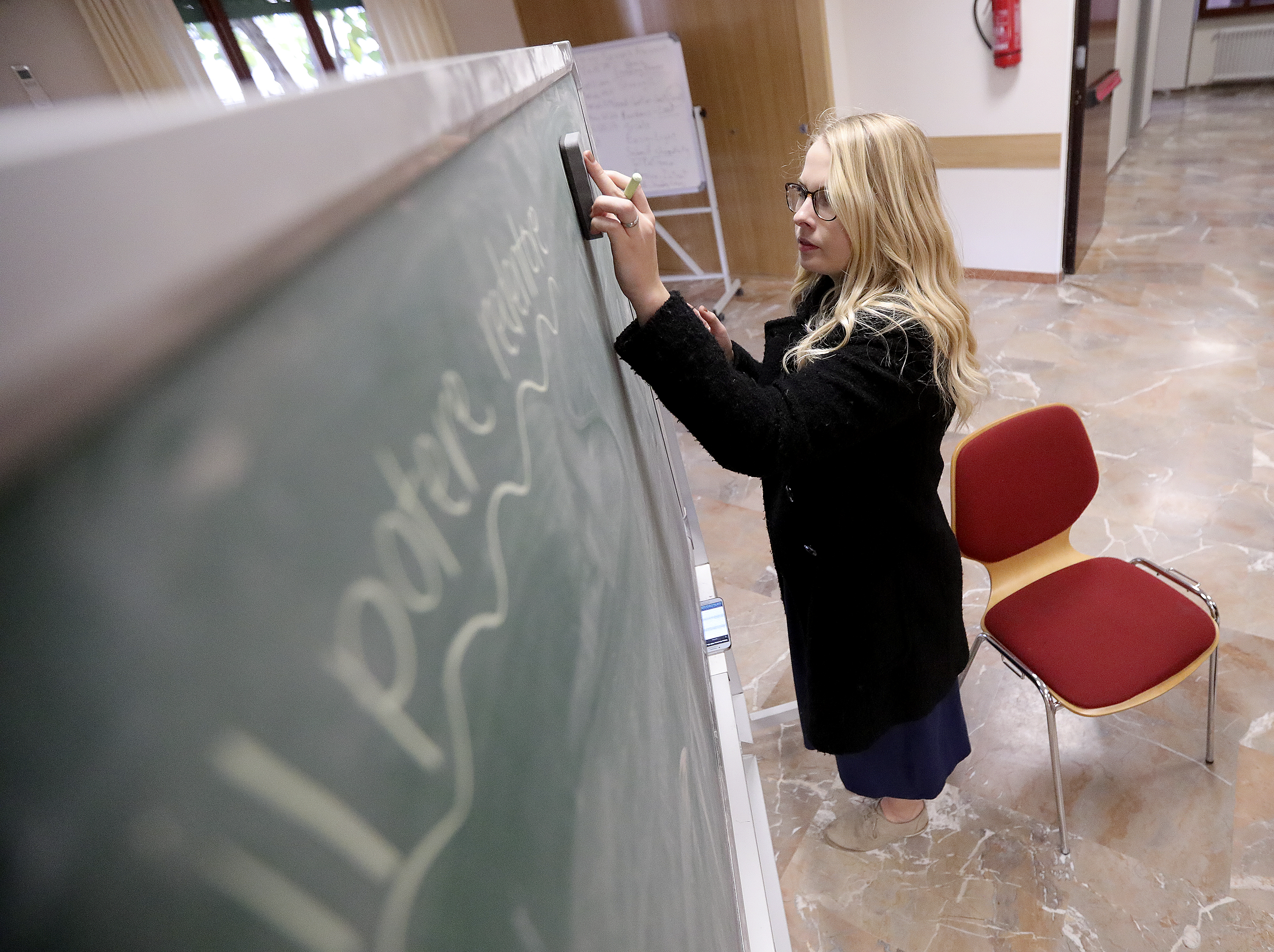 Sister Sadie Decker writes on a chalkboard while preparing to teach a lesson to a recent convert at the Rome 2nd/5th wards meetinghouse in Rome, Italy, on Saturday, Nov. 17, 2018.