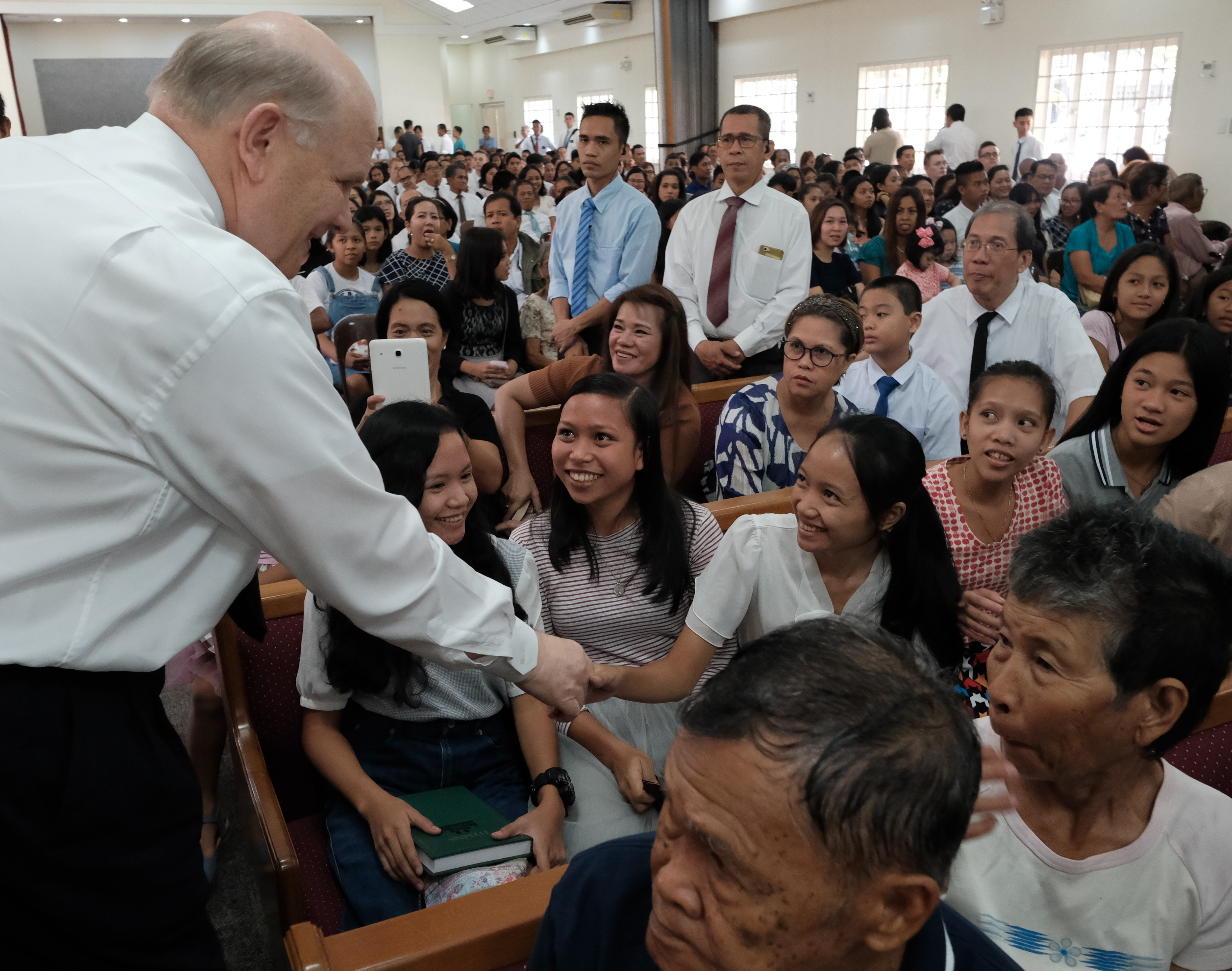 Elder Renlund greets members in Bacolod following a devotional in Bacolod, Philippines, during a recent visit to the island nation.