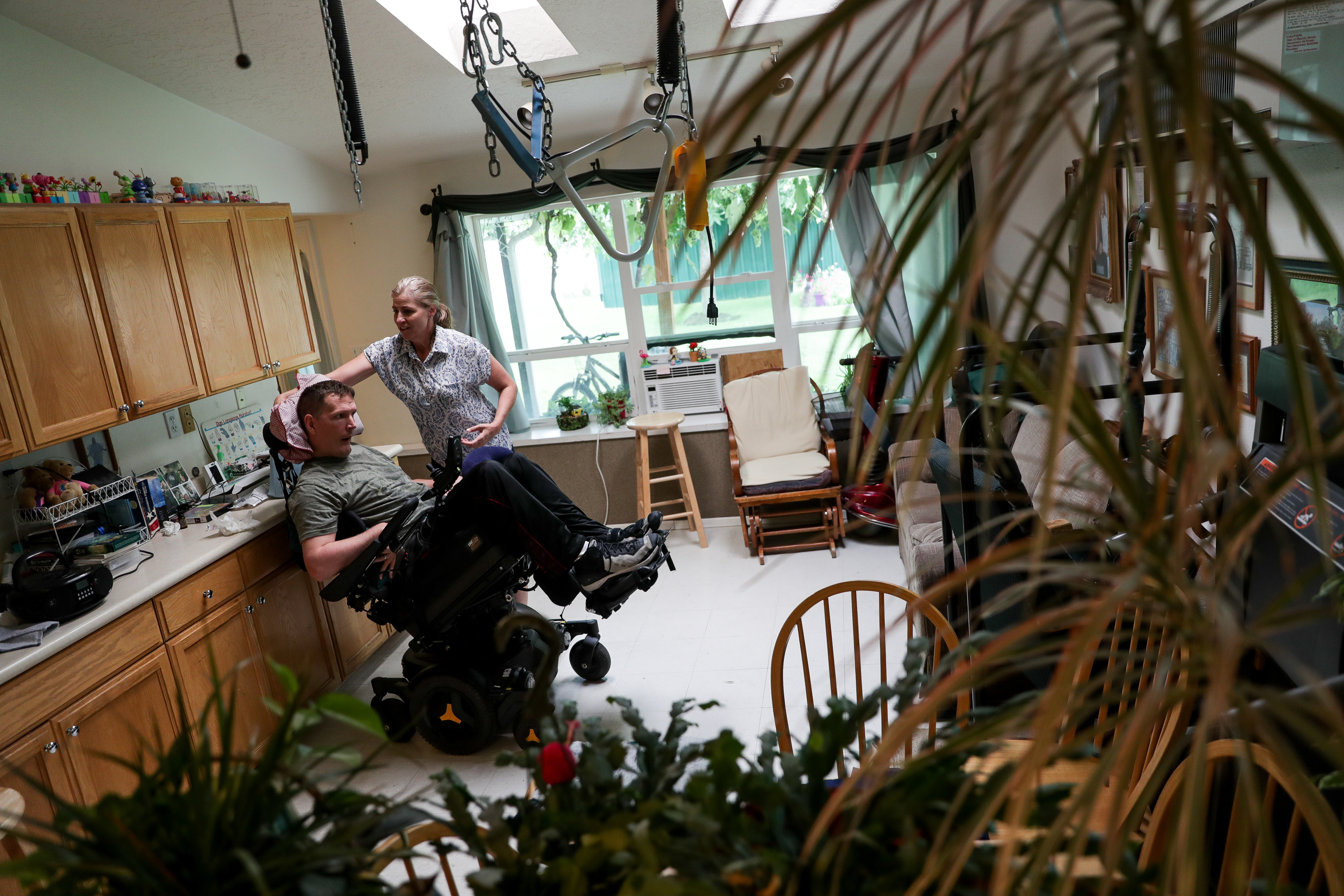 Wendy Tobey, who serves as a caregiver for Orin Voorheis, places a pillow behind his head at home in Pleasant Grove, Utah, on Tuesday, July 10, 2018.