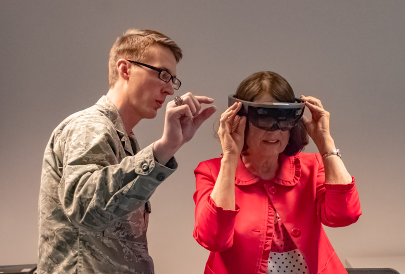 Connor Crandall demonstrates to Sister Kathryn S. Callister how to squeeze fingers together in the air to control the windows display on the screen of the Microsoft HoloLens that she is wearing.