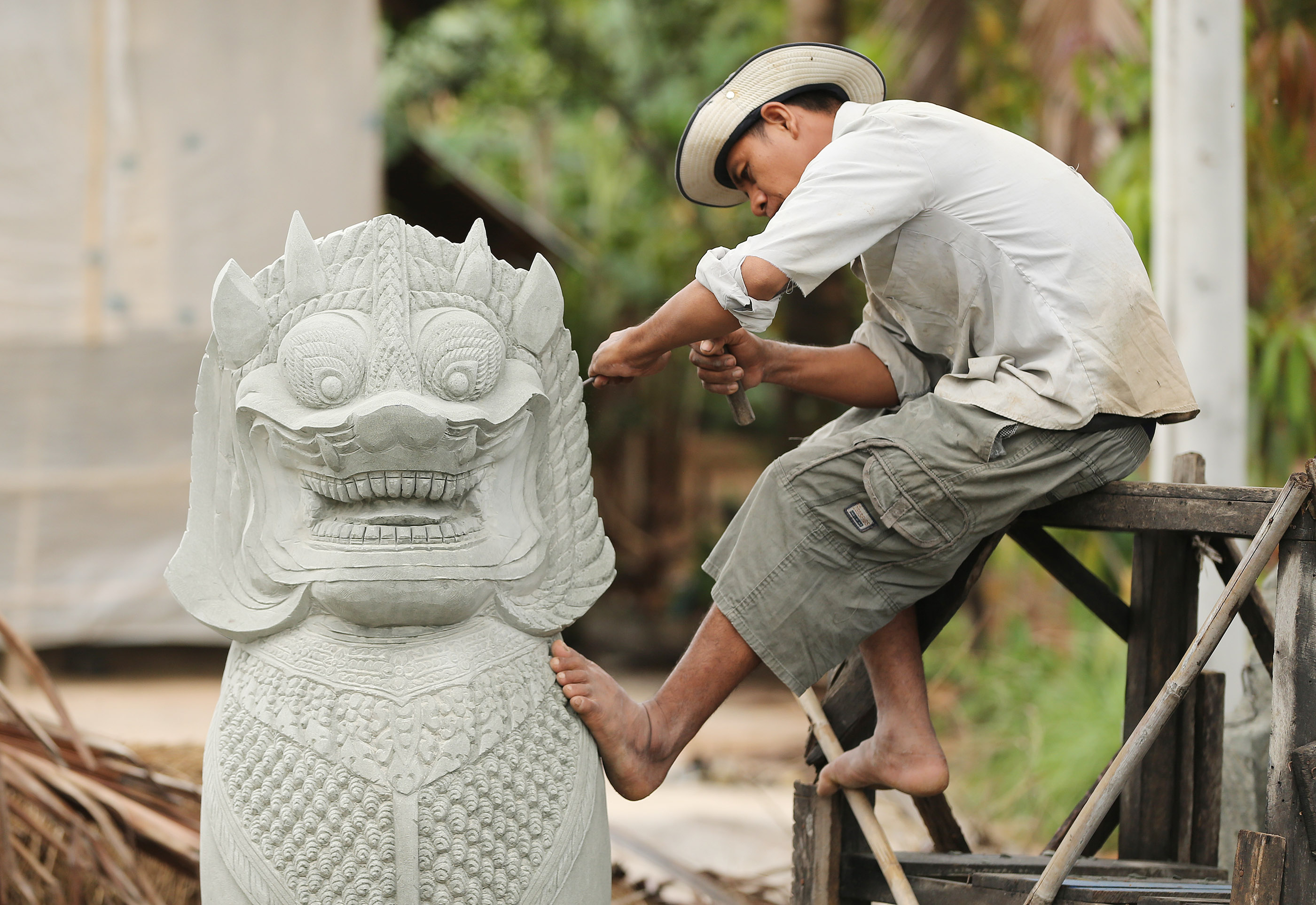 A sculptor works on a statue in Cambodia on April 28, 2018.