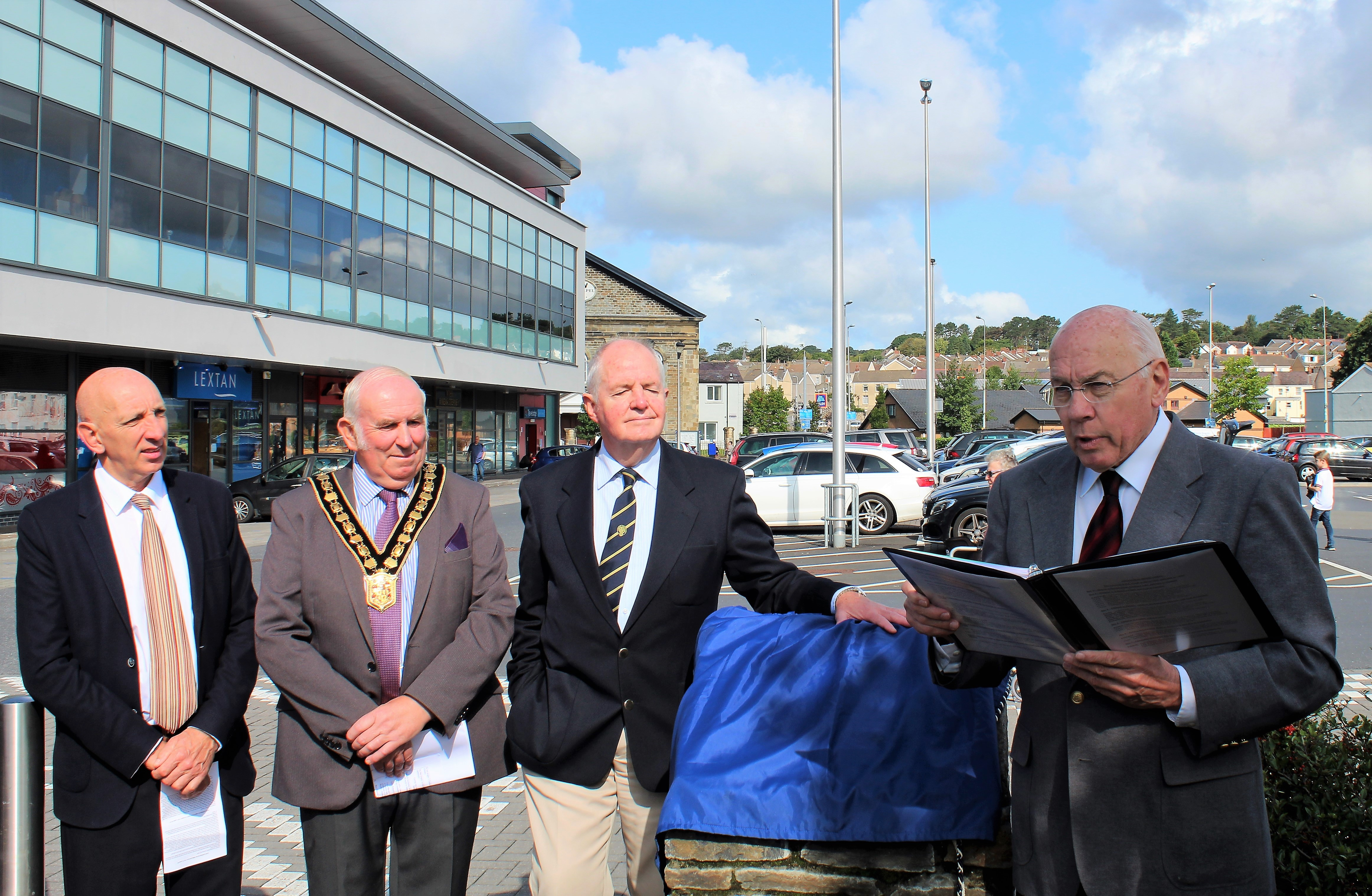 On the right, Dr. Ronald Dennis presents at the unveiling of the blue plaque to commemorate the historic Island Place Meeting House on Aug 25, 2018, in Llanelli, Wales. To his left stand a representative from Llanelli Community Heritage, the Chair of the Carmathenshire County Council, Councilor Mansel Charles, Plaid Cymru of Llanegwad, and Counselor W.E. Skinner, Labour, Bigyn Ward of Llanelli.