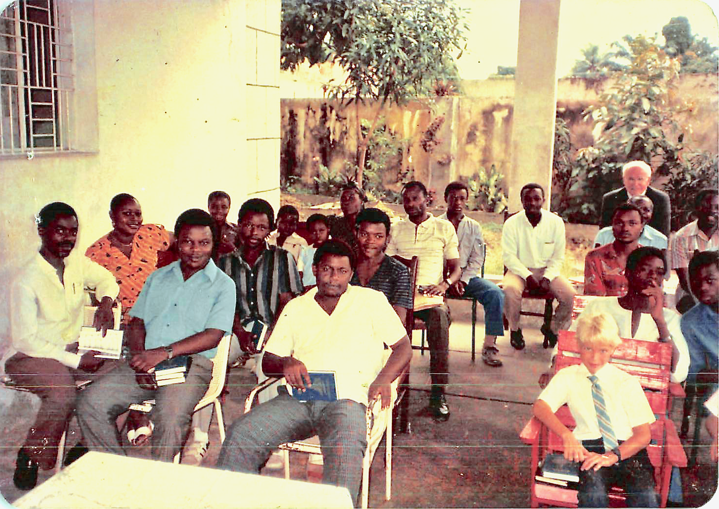 Members, missionaries and friends gather in the carport of Nkitabungi Mbuyi's home in early 1986, while awaiting official recognition of the Church from Zaire (now the Democratic Republic of the Congo) in 1986. The carport was used since attendance outgrew the available space in the Kinshasa home's living room.