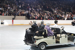 Four members who were present at the dedication of the first LDS chapel built in Calgary ride on golf carts during the cultural program held Saturday evening, Oct. 27, in celebration of the dedication of the Calgary Alberta Temple. The audience stood, cheered and applauded as about 20 of those members rode into the arena.