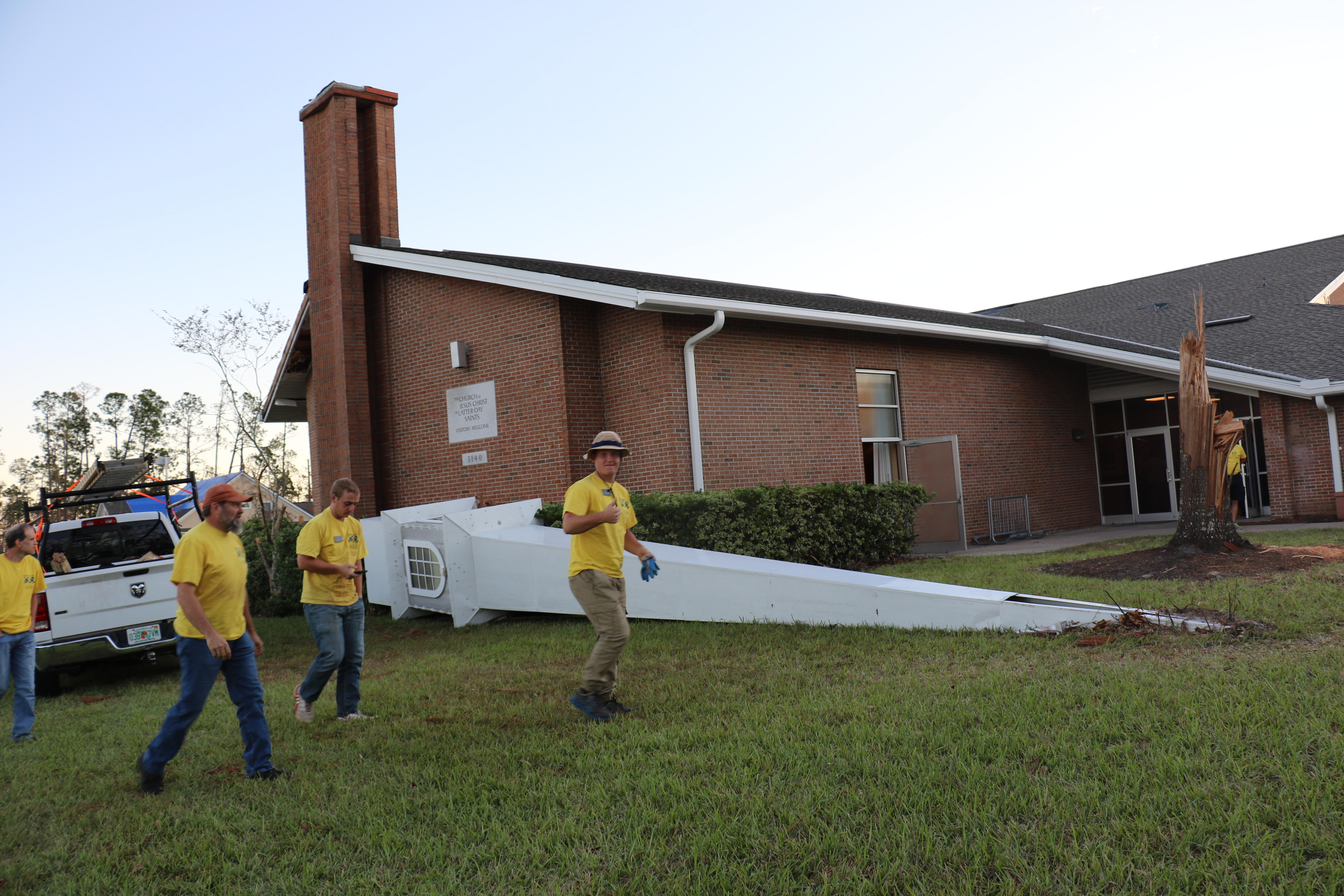 Helping Hands volunteers walk past fallen steeple outside the Panama City Florida Stake Center on Oct. 21, 2018.