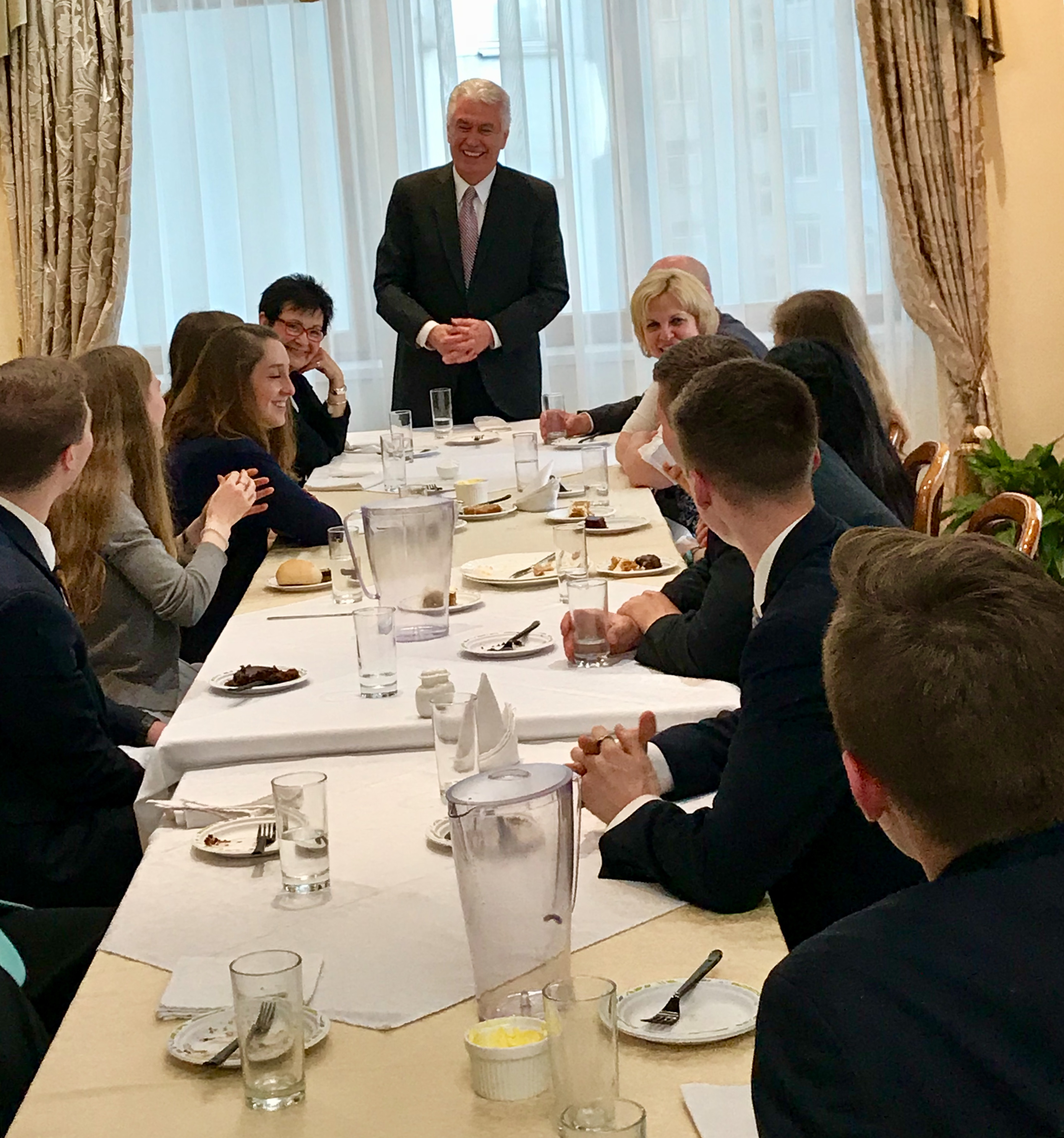 Elder Dieter F. Uchtdorf of the Quorum of the Twelve Apostles, standing at center, and Sister Harriet Uchtdorf, at his right, join a going-away dinner for 8 volunteers from the Russia St. Petersburg Mission at the mission home on April 25, 2018, prior to their departure to return home the next morning.