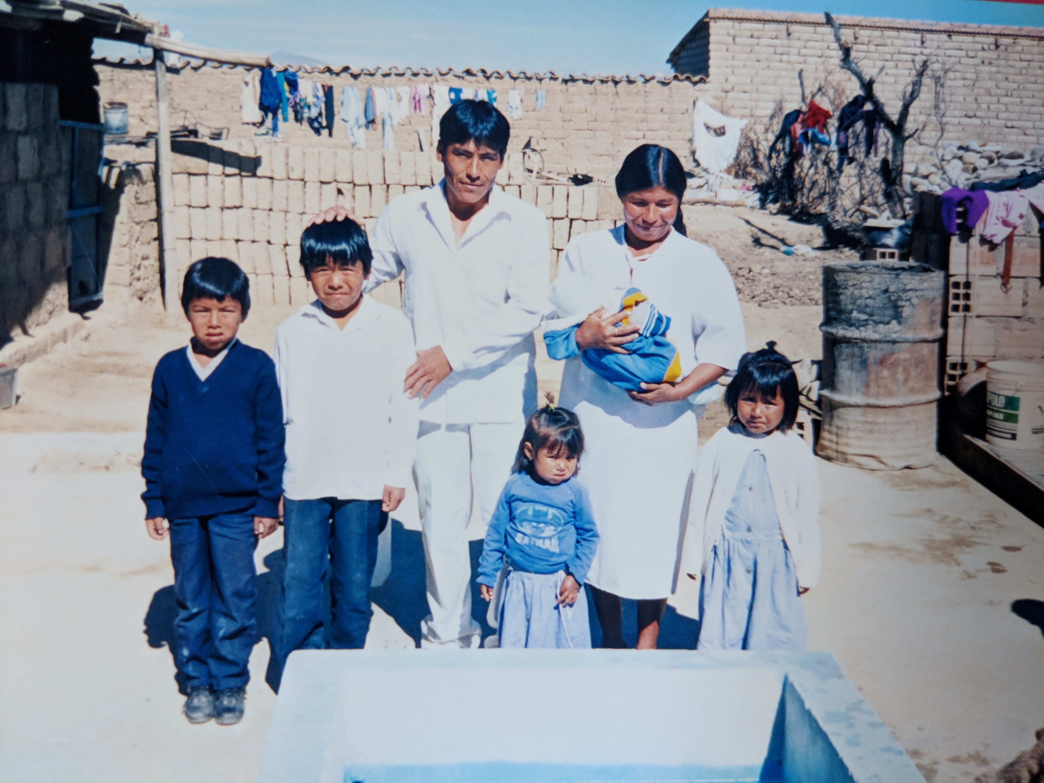 The Quispe family on their baptism day 20 years ago. They cleaned and painted a concrete pit in their front yard for their baptism.