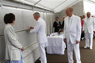 President Henry B. Eyring observes as Elder D. Todd Christofferson place mortar on the capstone of the El Salvador temple. Sister Eyring is at the left.