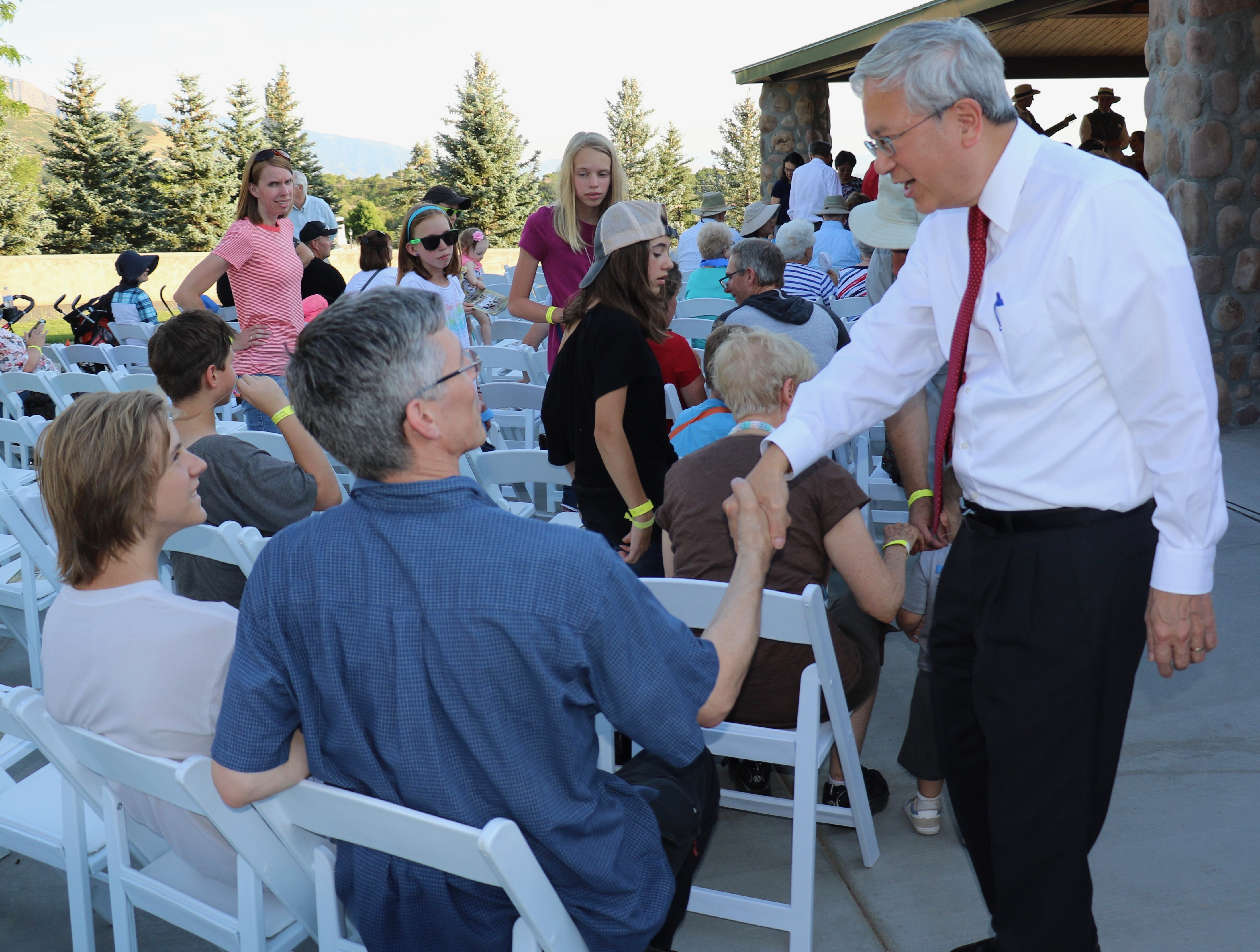 Elder Gerrit W. Gong of the Quorum of the Twelve Apostles greets guests prior to a pioneer-themed devotional at This Is the Place Heritage Park on July 16, 2018.