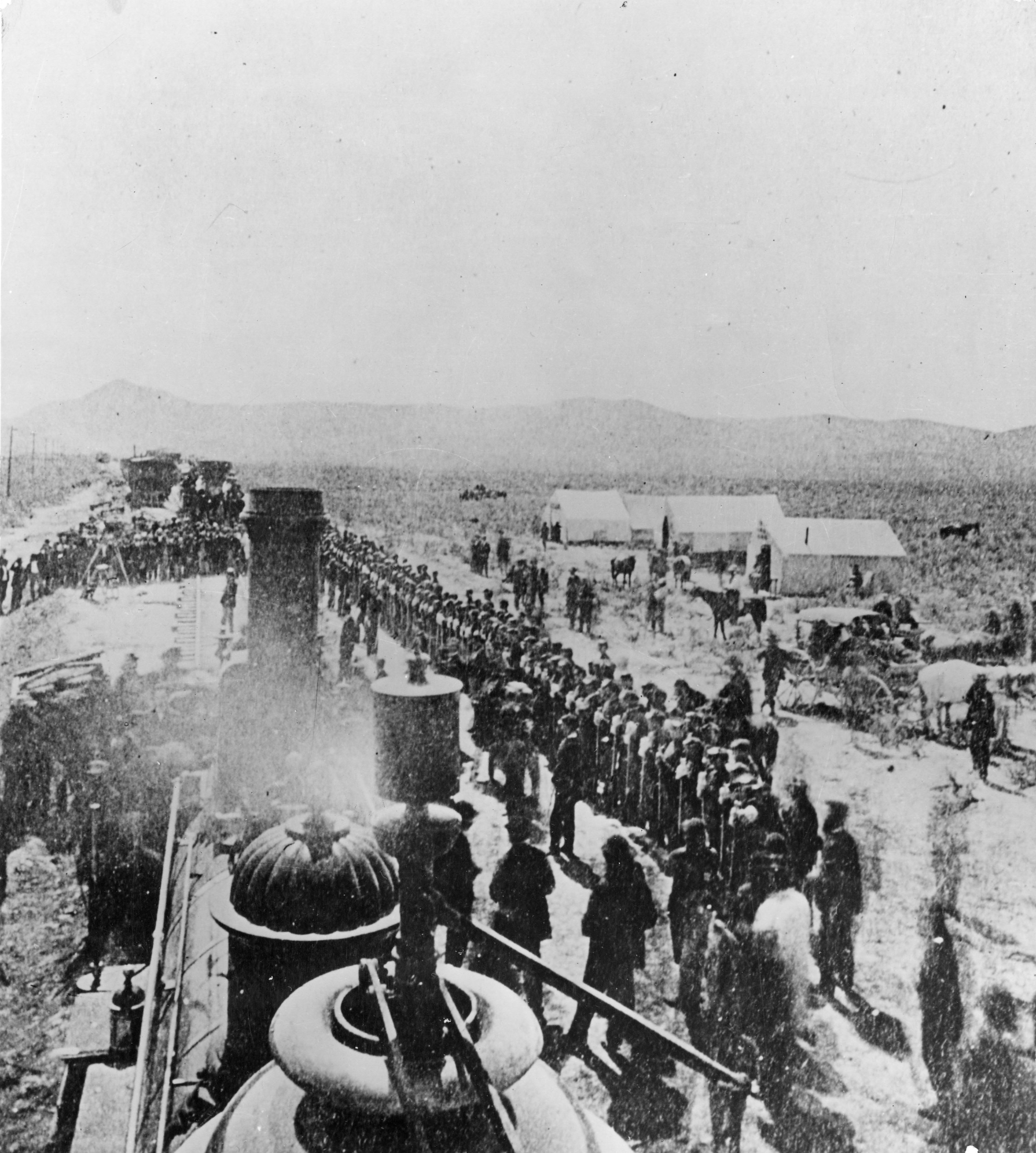 """A view at Promontory, Utah, May 10, 1869, during the """"Last Spike"""" ceremony when rails of the Central Pacific (now Southern Pacific) and the Union Pacific were joined to complete the first transcontinental railroad. The picture is taken from the U.P. locomotive #119, looking westward, and shows the four companies of the 21st Infantry in formation alongside the track of Central Pacific's locomotive, """"Jupiter,"""" with tent-buildings."""