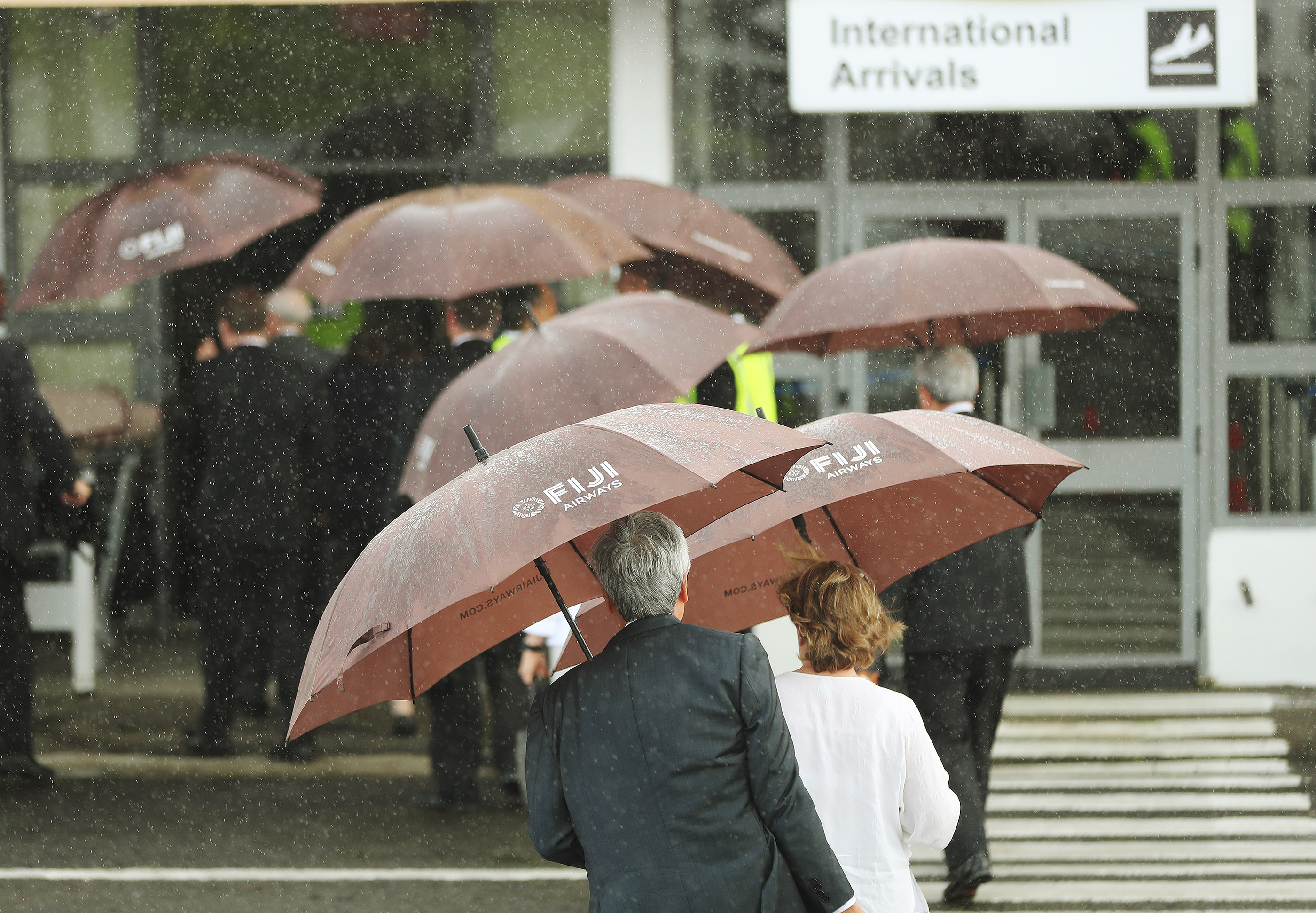President Russell M. Nelson of The Church of Jesus Christ of Latter-day Saints and other general authorities leave the airplane in the rain prior to a devotional at Ratu Cakobau Park stadium in Nausori, Fiji, on May 22, 2019.
