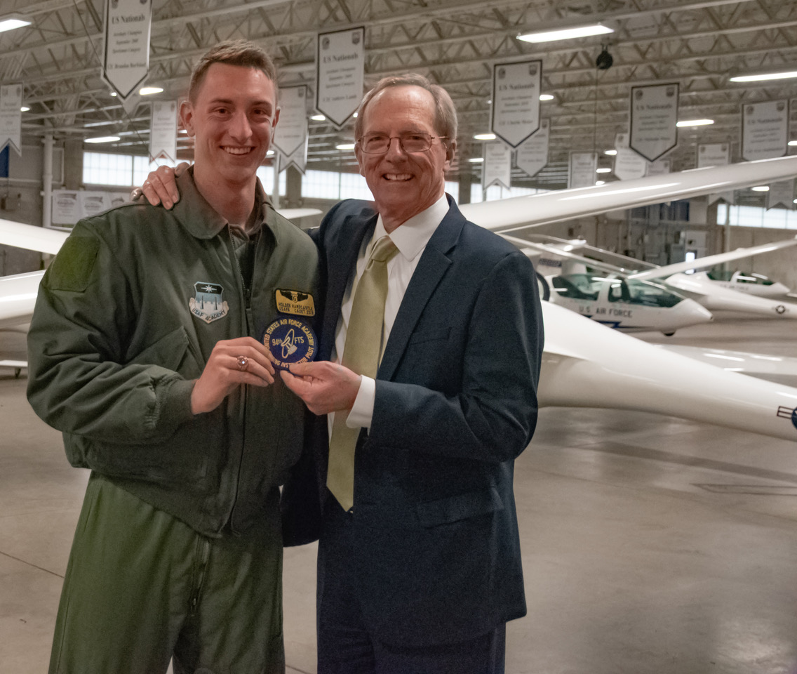 Cadet 2nd Class, Holden Hardcastle, who is a Soaring Instructor Pilot, presents Brother Tad R. Callister with an Air Force commemorative patch.