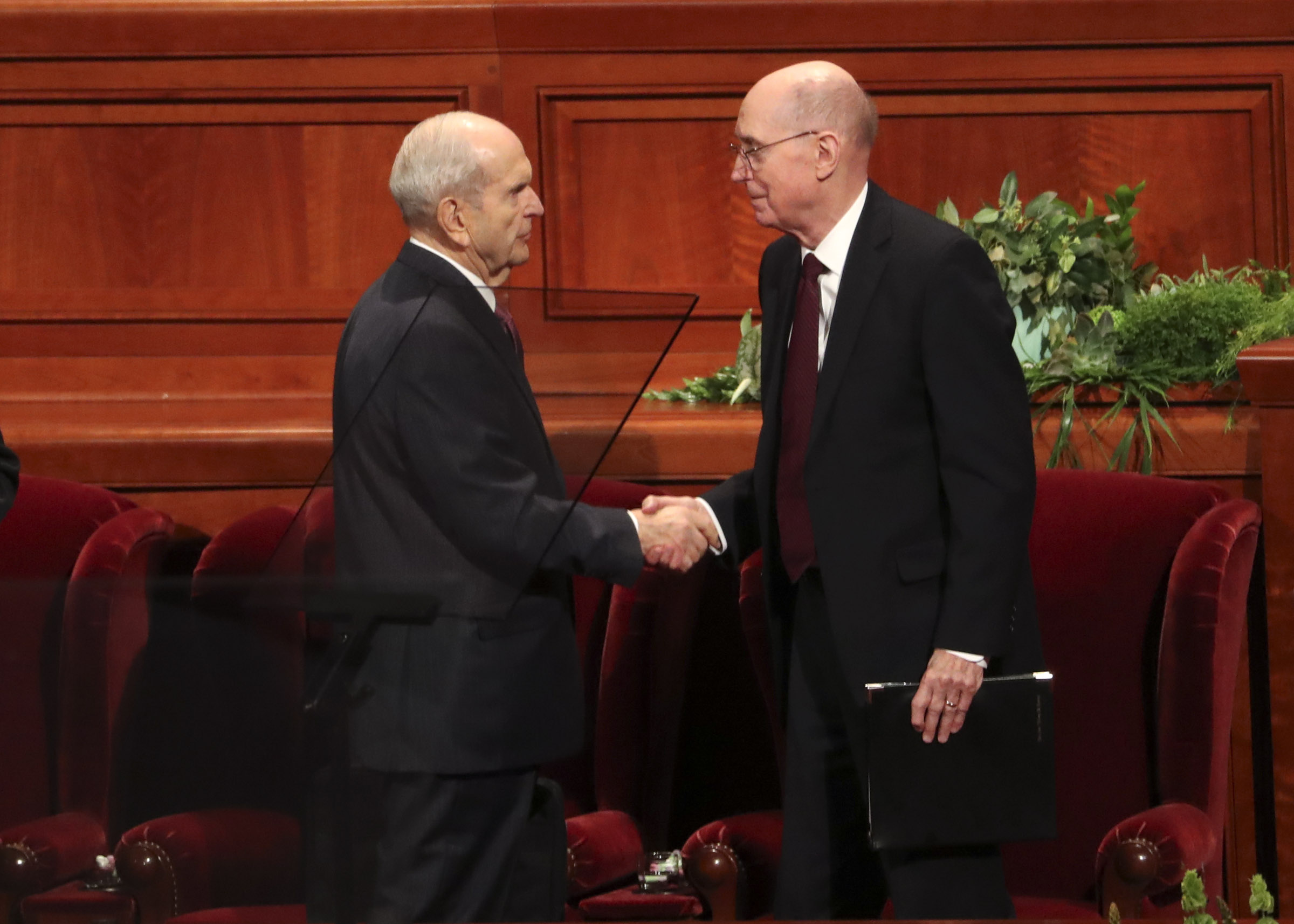 President Russell M. Nelson of The Church of Jesus Christ of Latter-day Saints, left, shakes hands with President Henry B. Eyring, second counselor in the First Presidency, as they stand to leave the Conference Center in Salt Lake City following the morning session of general conference on Saturday, April 6, 2019.