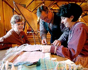 Sister Jean Brimley and Elder Kent and Sister Jeanette Staheli work on weaving done in the manner of the 1840s residents of Nauvoo.