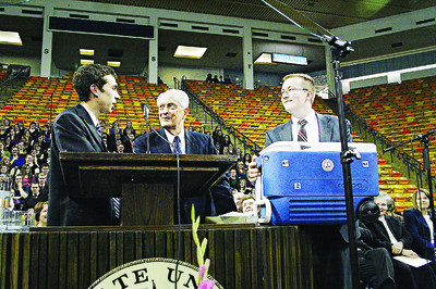 """Utah State students Colby Page, left, and Joseph Irvine, right, present Elder Robert D. Hales with a cooler filled with """"Aggie Blue Ice Cream,"""" a favorite campus confection. Elder Hales spoke at a fireside on the Utah State University campus."""