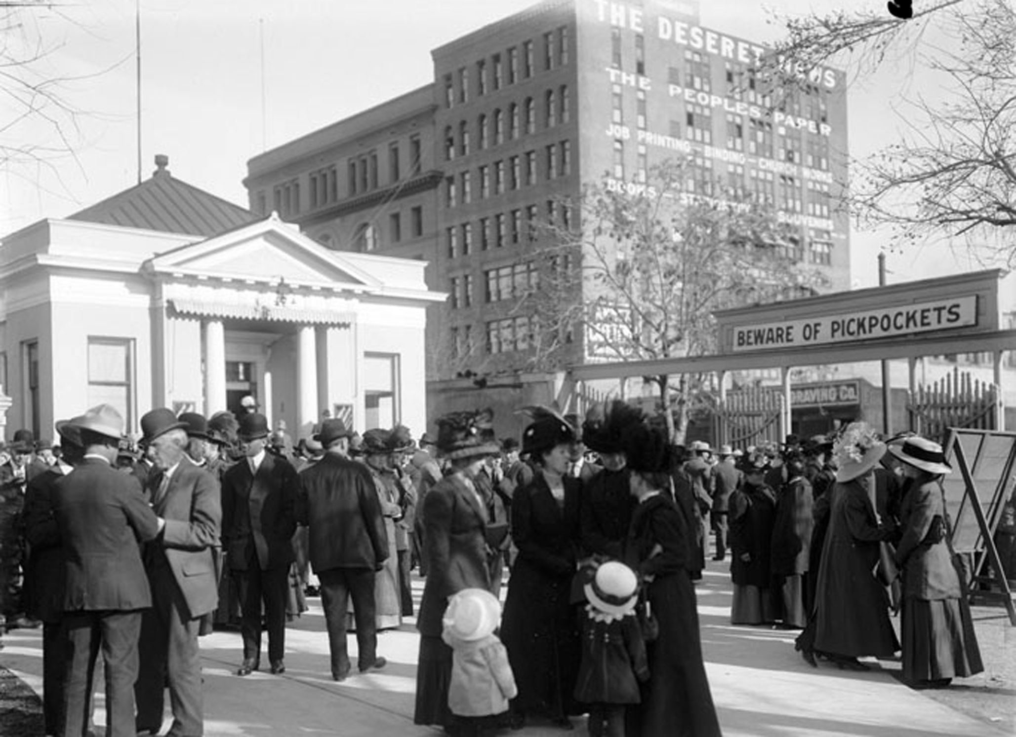 """Crowds gather for General Conference in April of 1911. Note the sign above the entrance to Temple Square """"Beware of Pickpockets"""" The old Deseret News building is seen across the street. Deseret News Archives"""