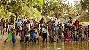 Children in Lowama, Sierra Leone, follow visiting Church members to the riverbank to bid farewell. Their families look forward to a new well, constructed with the help of LDS Charities, that will soon be operational there.