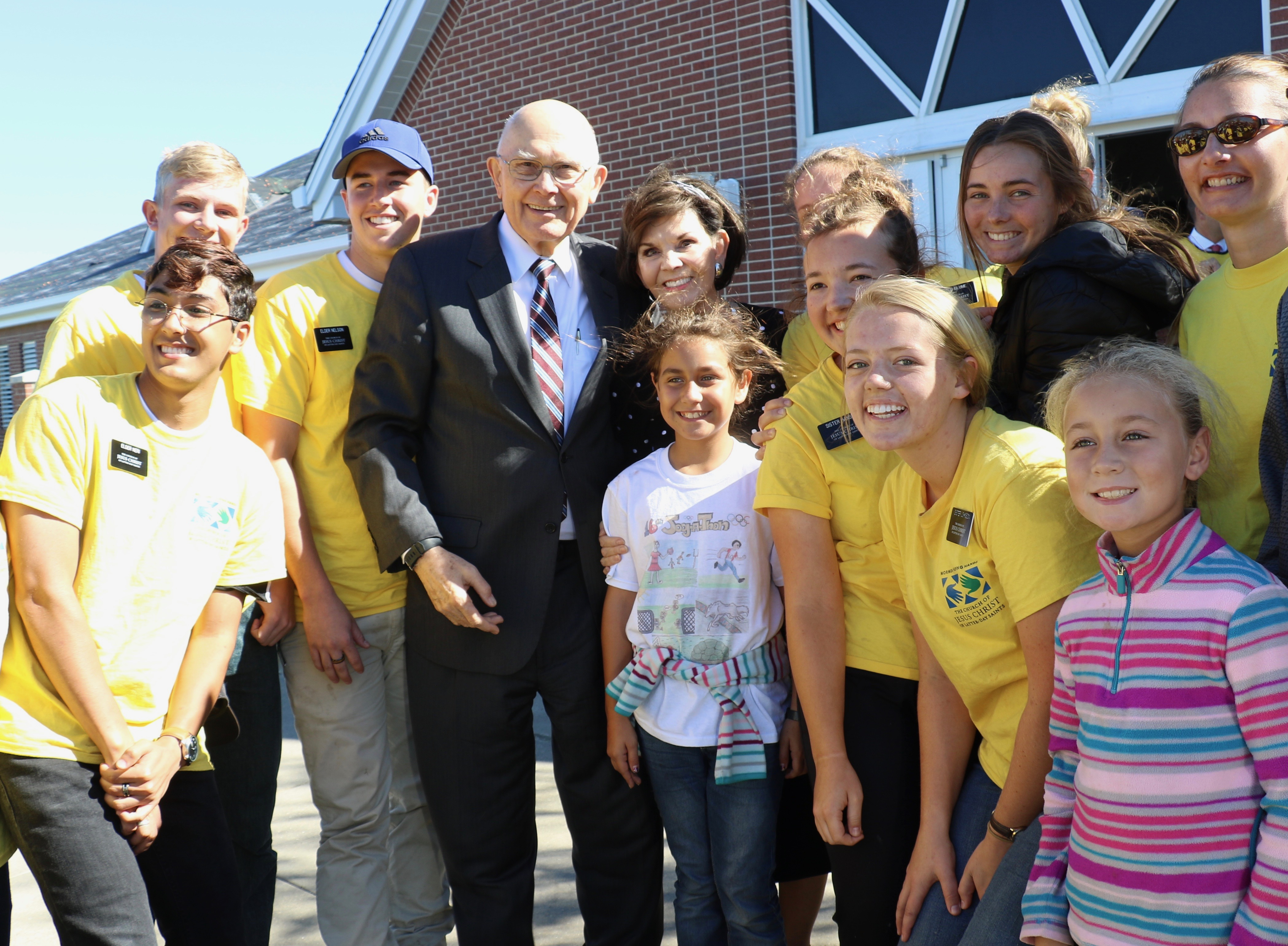 President Dallin H. Oaks of The Church of Jesus Christ of Latter-day Saints and Sister Kristen Oaks enjoy posing for picture with missionaries and youth outside the Callaway Ward Meetinghouse in Florida.