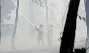 Firefighters use a hose to quench embers at a fire at Chum Creek, near Healseville, north east of Melbourne, Australia Tuesday, Feb. 10, 2009. Officials believe arson may be behind at least some of the more than 400 fires that tore a destructive path across a vast swath of southern Victoria state over the weekend.(AP Photo/Rick Rycroft)