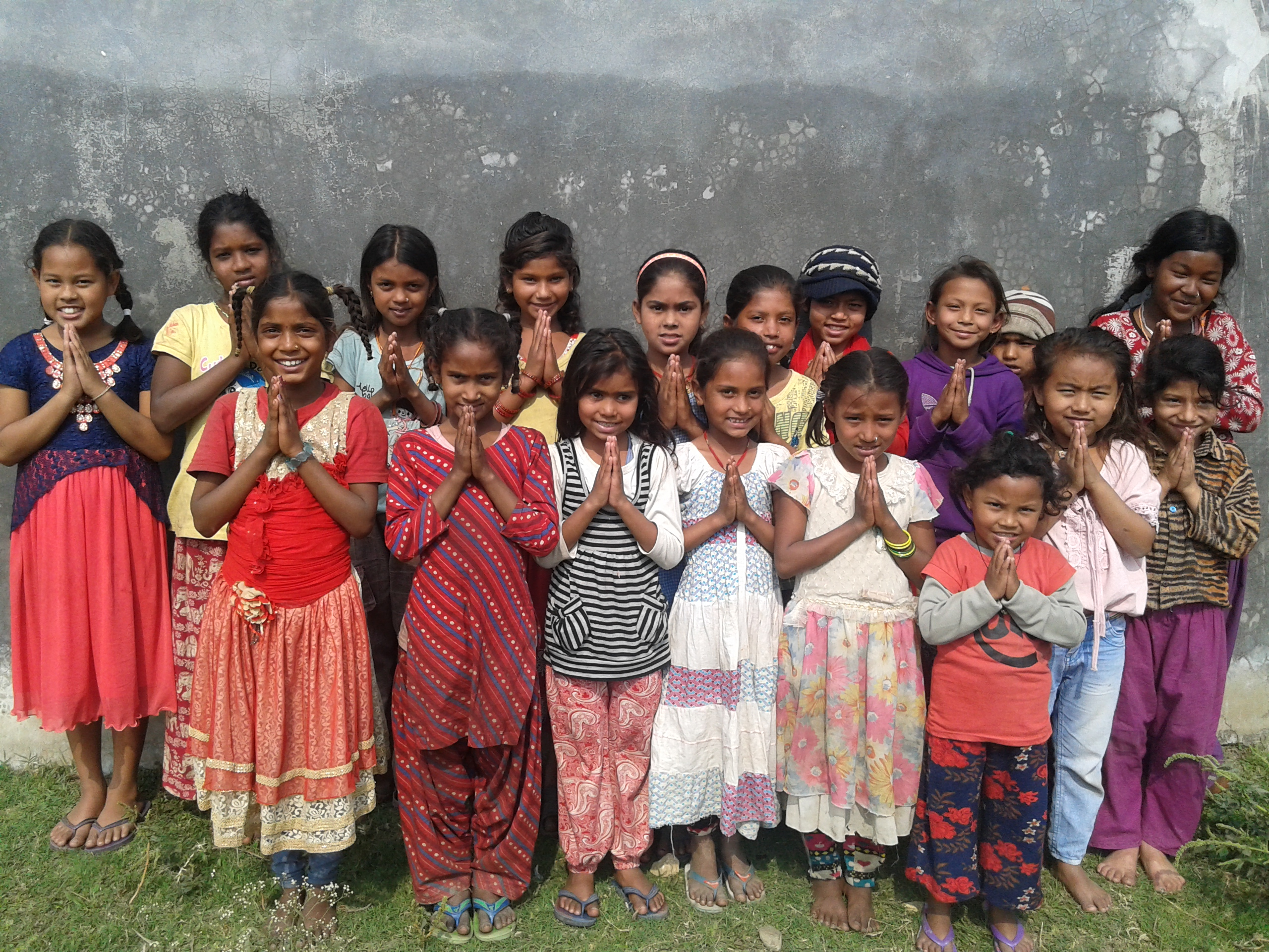 Students in the slums gather and show the traditional namaste greeting of Nepal.