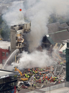 Rescue workers work to extinguish a fire at a collapsed building in central Christchurch, New Zealand, Tuesday, Feb. 22, 2011. A powerful earthquake collapsed buildings at the height of a busy workday Tuesday, killing and trapping dozens in one of the country's worst natural disasters.