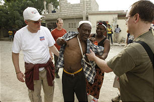 Doctors Jeff Randle, left, and Jeremy Booth, right, help a man on the streets in Port-au-Prince, Haiti. The LDS doctors are among those who have rushed to Haiti to provide relief and aid for Haitians suffering the effects of a powerful earthquake.
