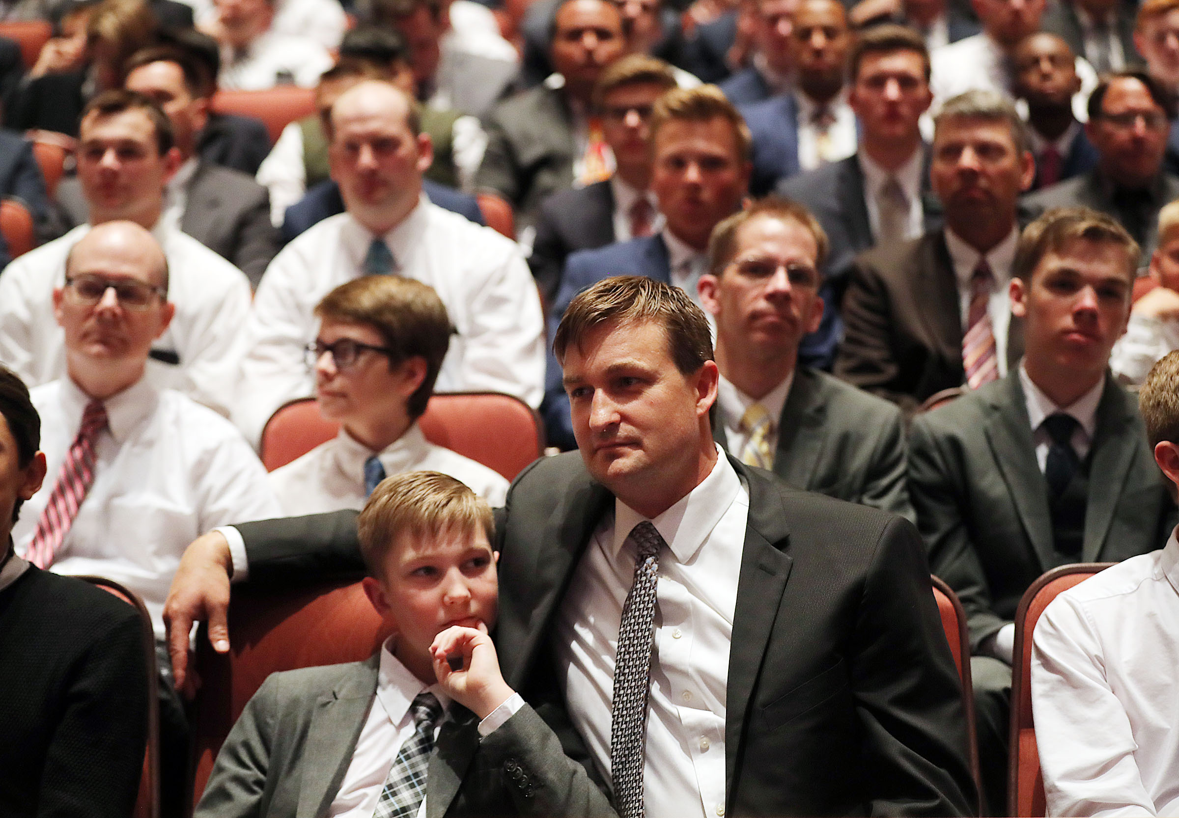 Scott Johnson and his son, Charles, of Denton, Texas, listen during the priesthood session of the 189th Annual General Conference of The Church of Jesus Christ of Latter-day Saints in the Conference Center in Salt Lake City on Saturday, April 6, 2019.