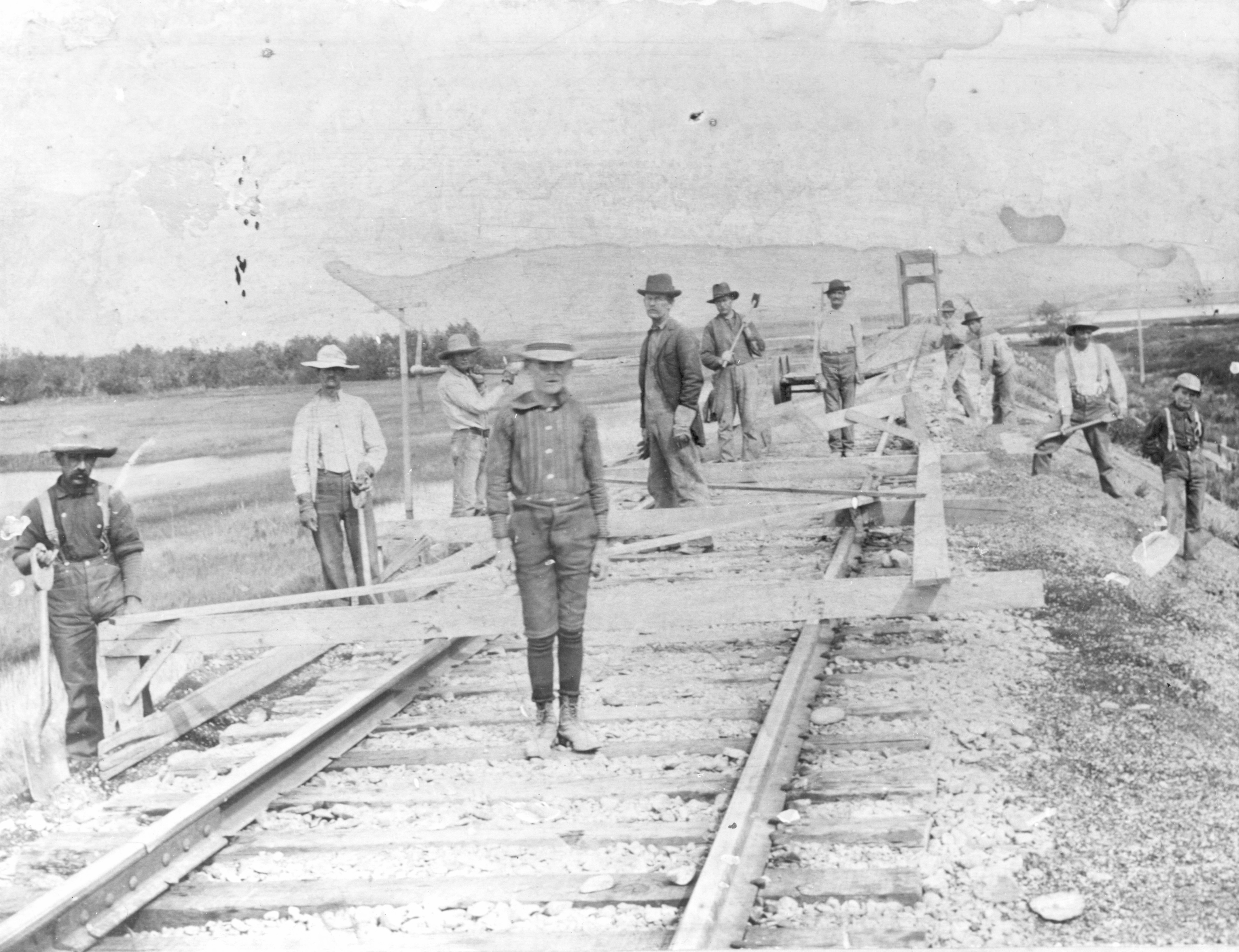 Workers, including men and boys, work on a Central Pacific Railroad grade and bridge over Bear River at Corinne, looking east. The Wasatch Range can be seen in the background.