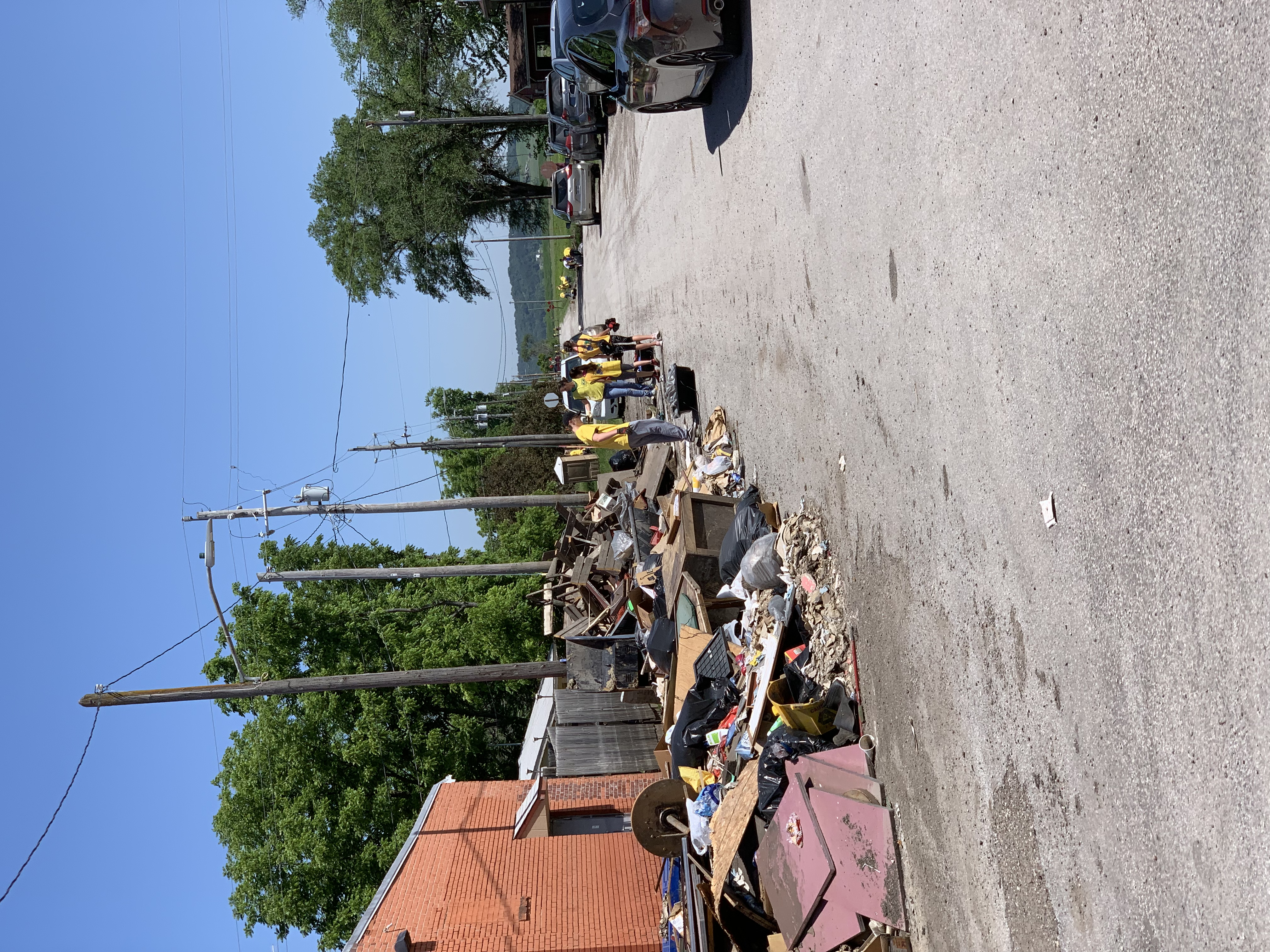 Youth in yellow Helping Hands shirts clear the streets of debris on June 10, 2019. March rainfall and snowmelt left parts of Iowa in as much as 10 feet of water, devastating homes, farmland and roads.