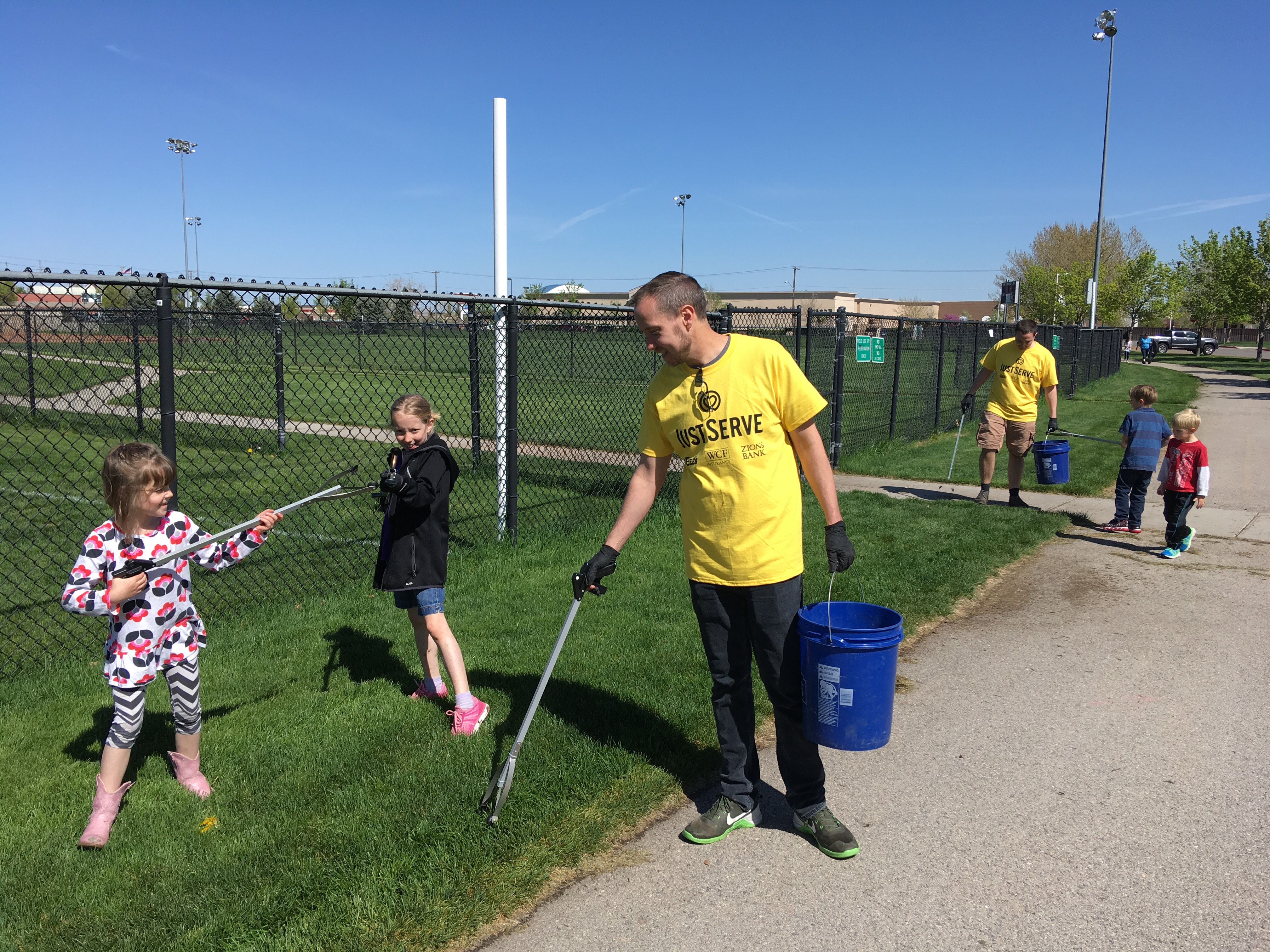 Families work together at a park in the Salt Lake area as part of the Salt Lake Bees/JustServe day of service.