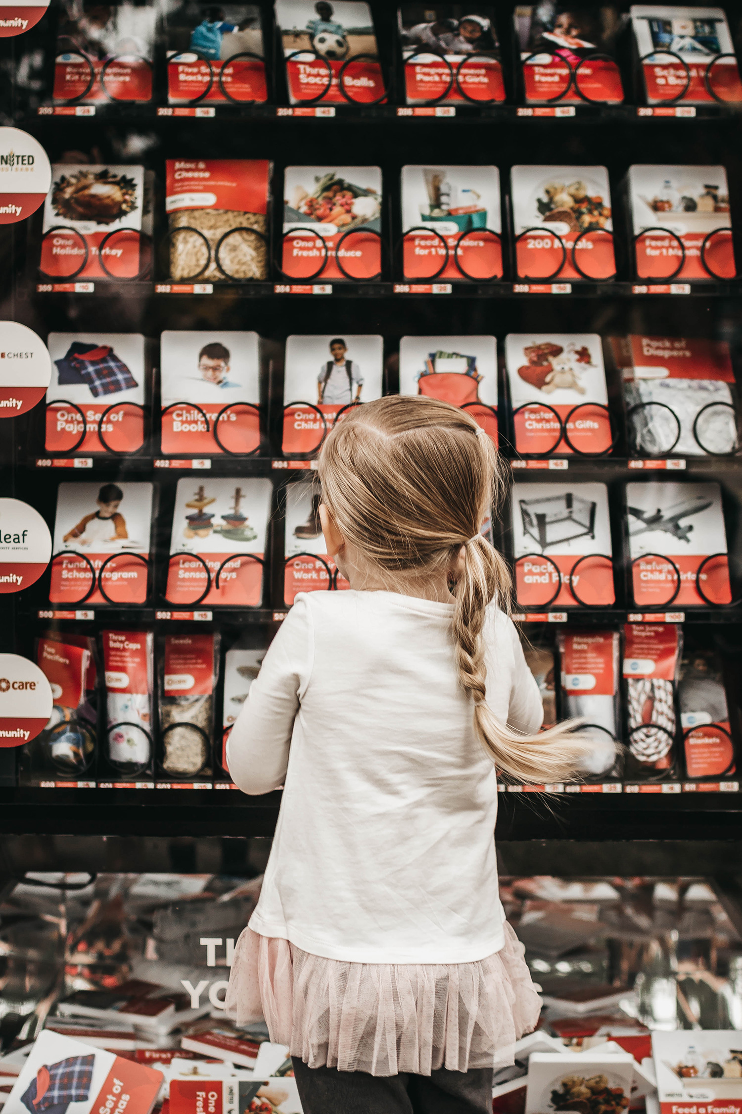 "A child looks through the selection of donations available in a #LightTheWorld ""giving machine"" in the lobby of the Joseph Smith Memorial Building in Salt Lake City."