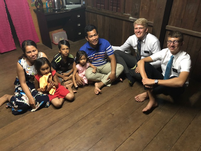Elders Bailey (right) and Christiansen meet with a family at their small shop.