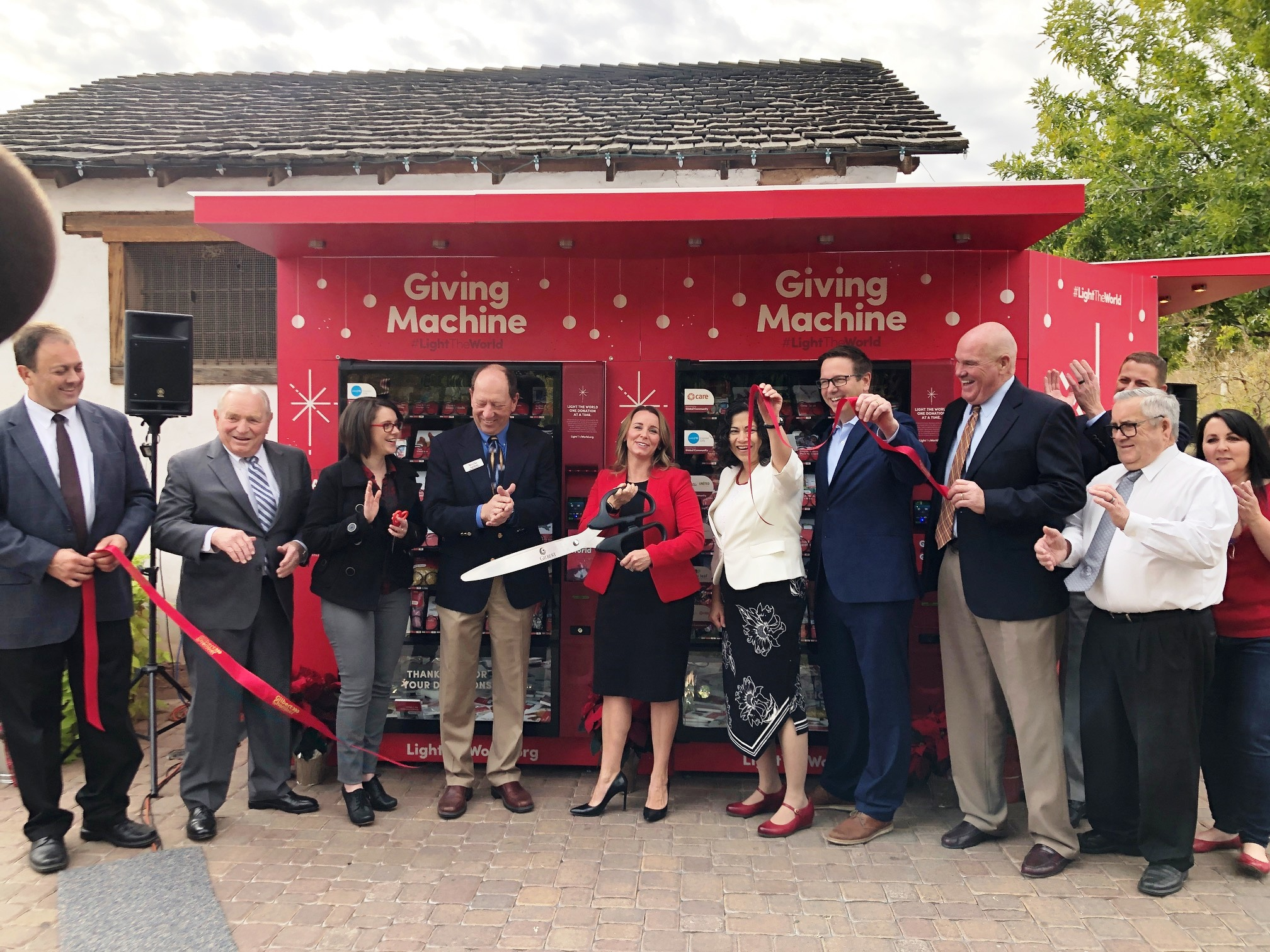 Gilbert Mayor Jenn Daniels cuts the ribbon for the opening of the giving machines on Thursday, Nov. 29, accompanied by Sister Reyna Aburto and leaders of local nonprofits that will benefit from donations made in Gilbert, Arizona. The giving machines are part of the Church's popular #LightTheWorld campaign.