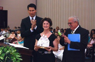 Patricia Harrison, deputy county executive of Fairfax County, receives the 2011 Family Values Award from U.S. Congressman Gerry Connolly as President Jon Dionne (background), first counselor in the Centreville stake presidency, applauds.