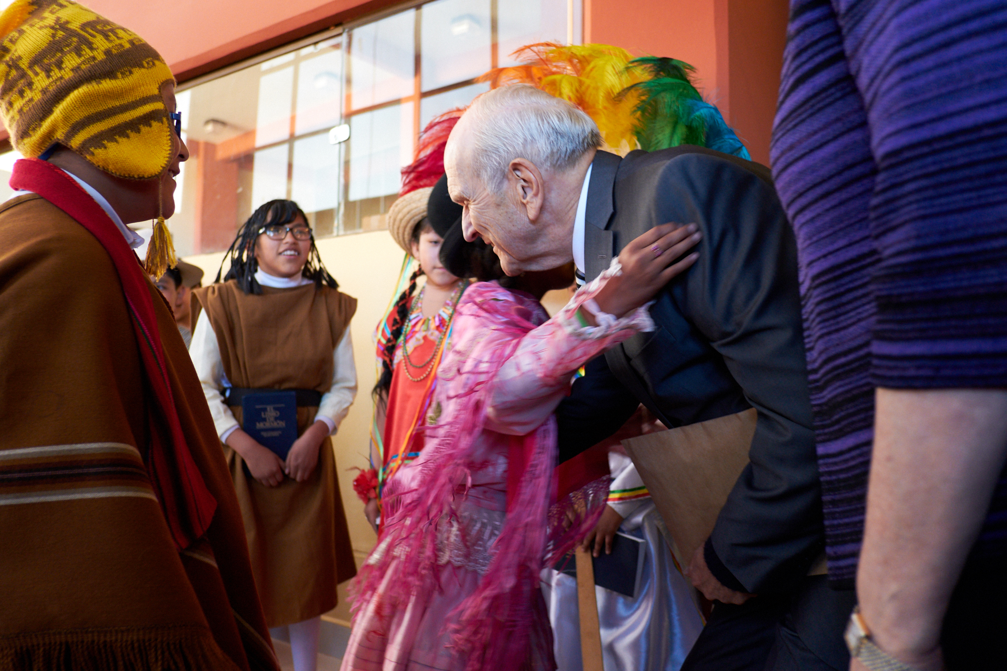 "President Russell M. Nelson and his wife, Sister Wendy Nelson, are greeted by Latter-day Saint children in traditional Bolivian dress prior to the Oct. 21, 2018, devotional at the Polideportivo Heroes de Octobre in El Alto, Bolivia. The children sang ""Follow the Prophet."""