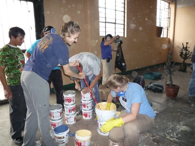 Two sister missionaries mix some paint that will be used on the interior living quarters of the shelter.