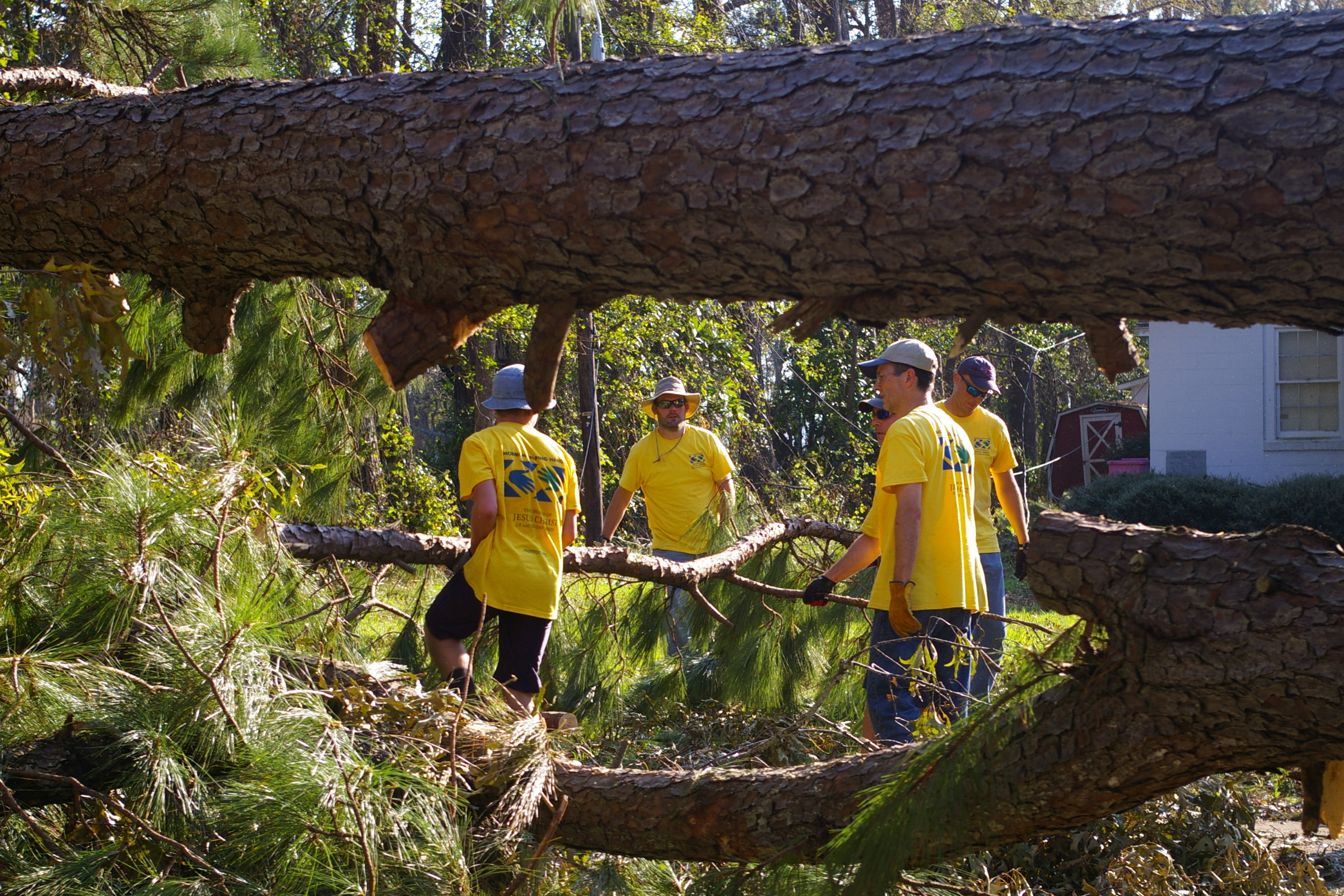 Church-sponsored Helping Hands crews clear out branches and fallen trees outside hurricane-impacted home in Wilmington, North Carolina.