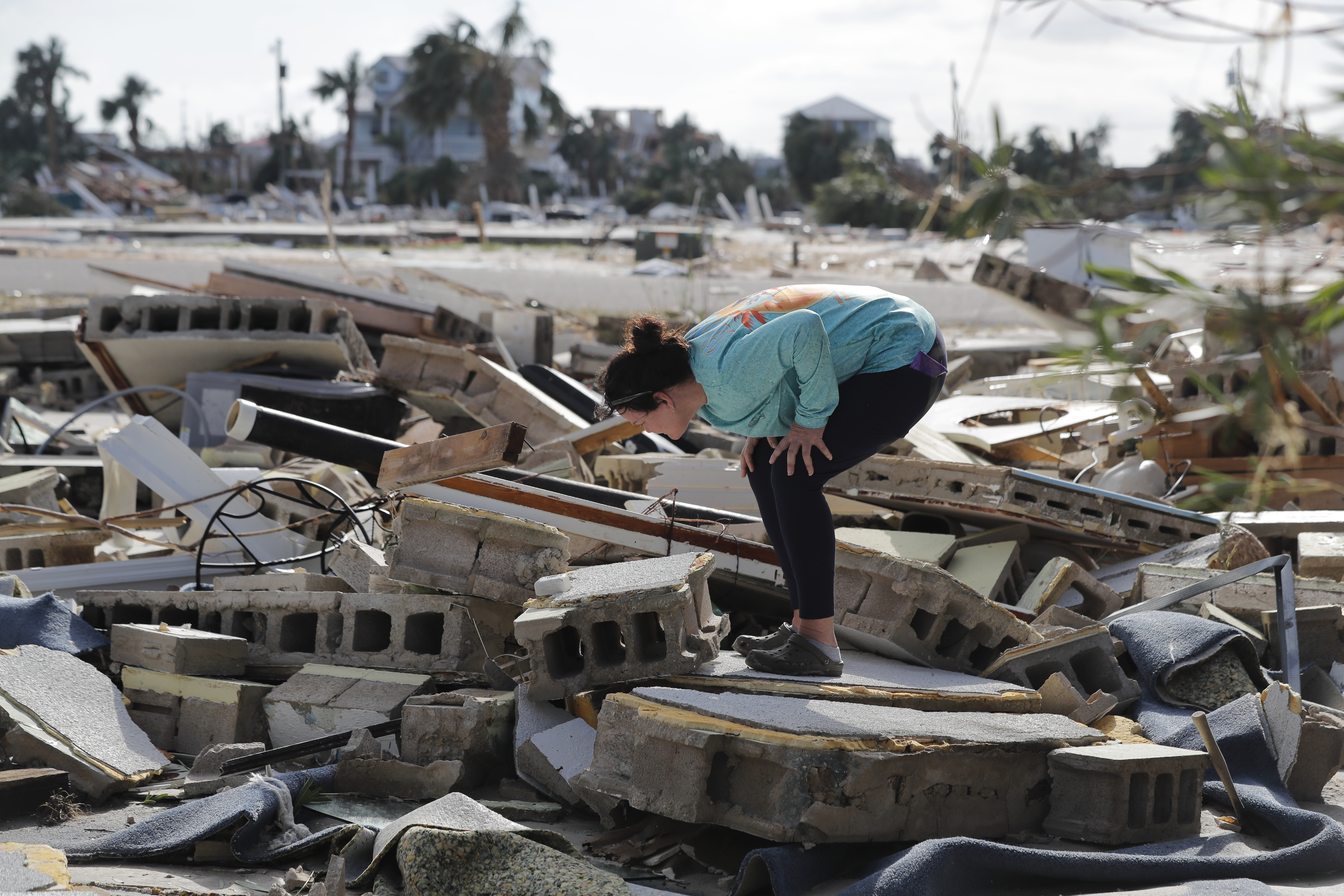 Mishelle McPherson looks for her friend in the rubble of her home, since she knows she stayed behind in the home during Hurricane Michael, in Mexico Beach, Fla., Thursday, Oct. 11, 2018.