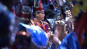 Dancers don Aztec-style regalia.