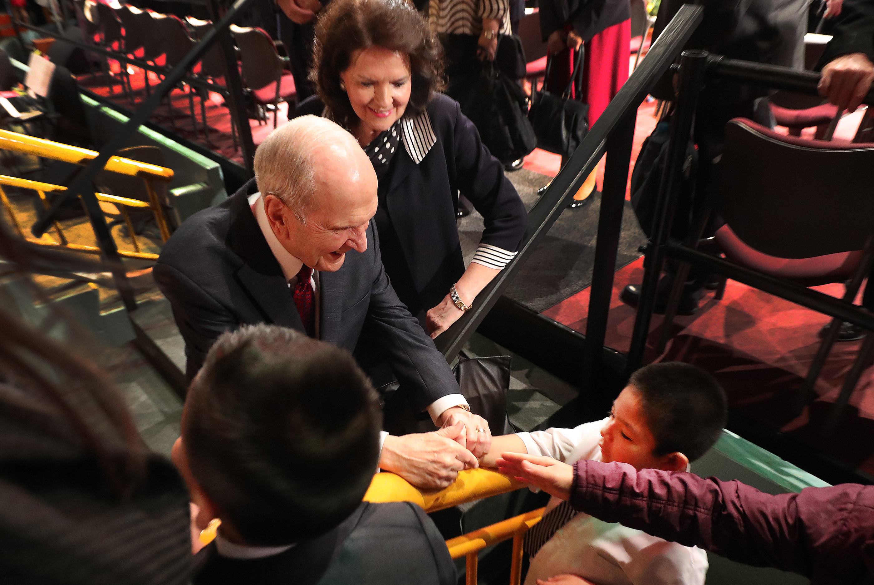 President Russell M. Nelson of The Church of Jesus Christ of Latter-day Saints and his wife, Sister Wendy Nelson, greet a youngster after a devotional in Lima, Peru, on Oct. 20, 2018.