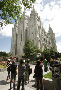 Sister missionaries explain the rich history of the Salt Lake Temple to visitors at Temple Square.