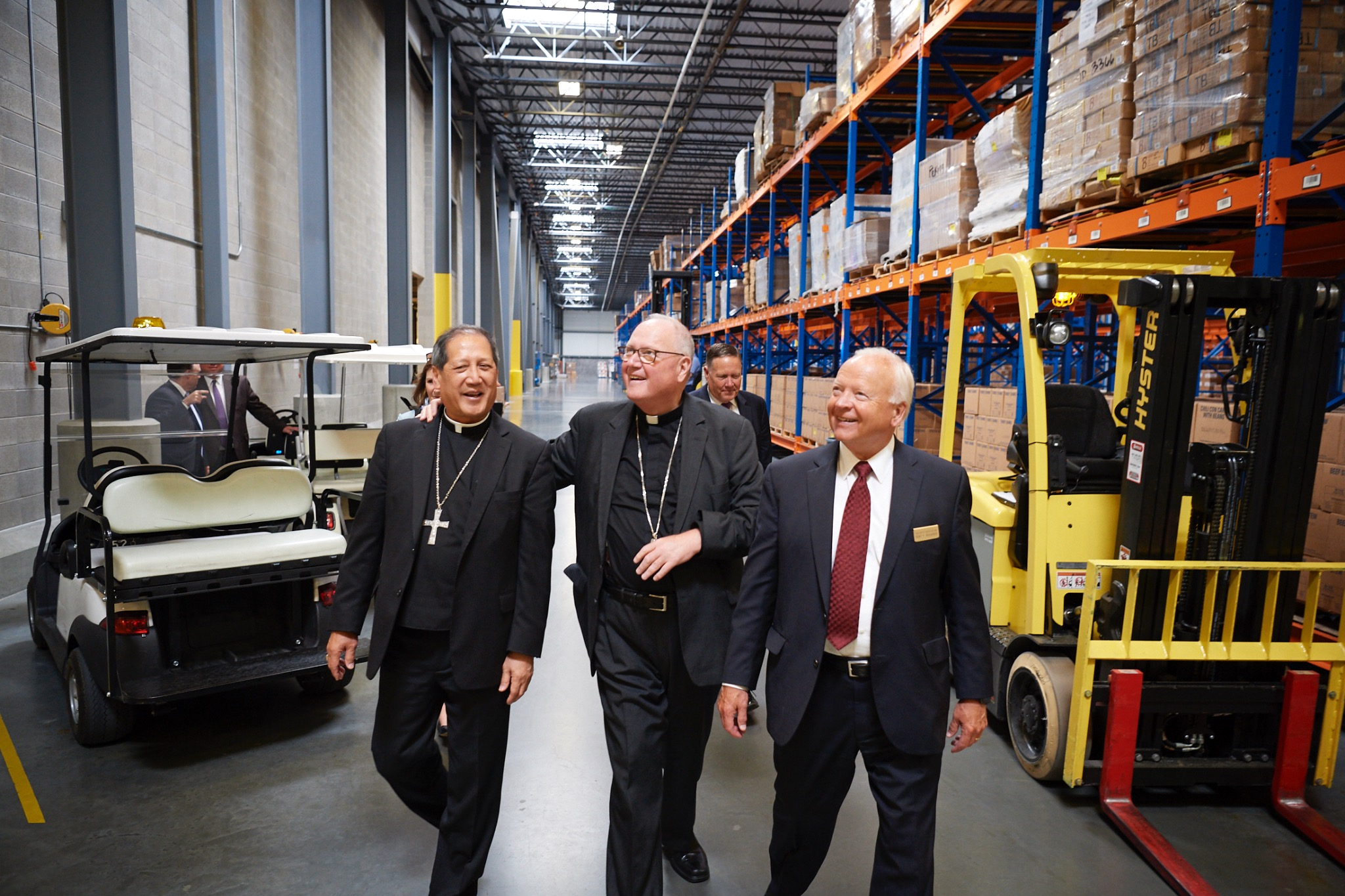 Elder Kent F. Richards, right, gives Catholic leaders Timothy Cardinal Dolan, center, and Bishop Oscar A. Solis a tour of the Bishops' Central Storehouse facilities in Salt Lake City, Utah, on Monday, July 1, 2019.