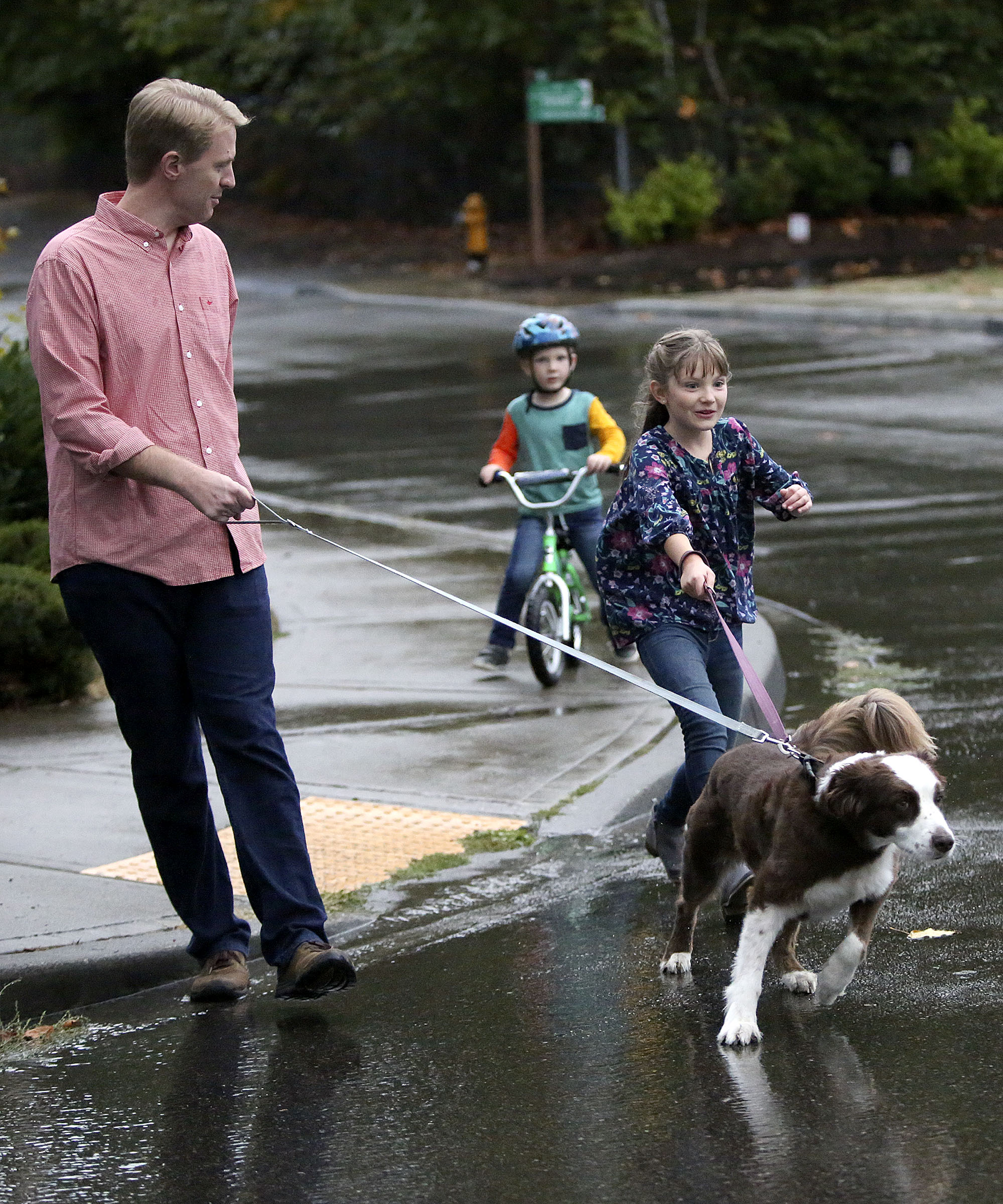 Justin, Daniel and Emilia Allen walk home with their dog Lou in Renton, Wash., on Friday, Sept. 14, 2018.