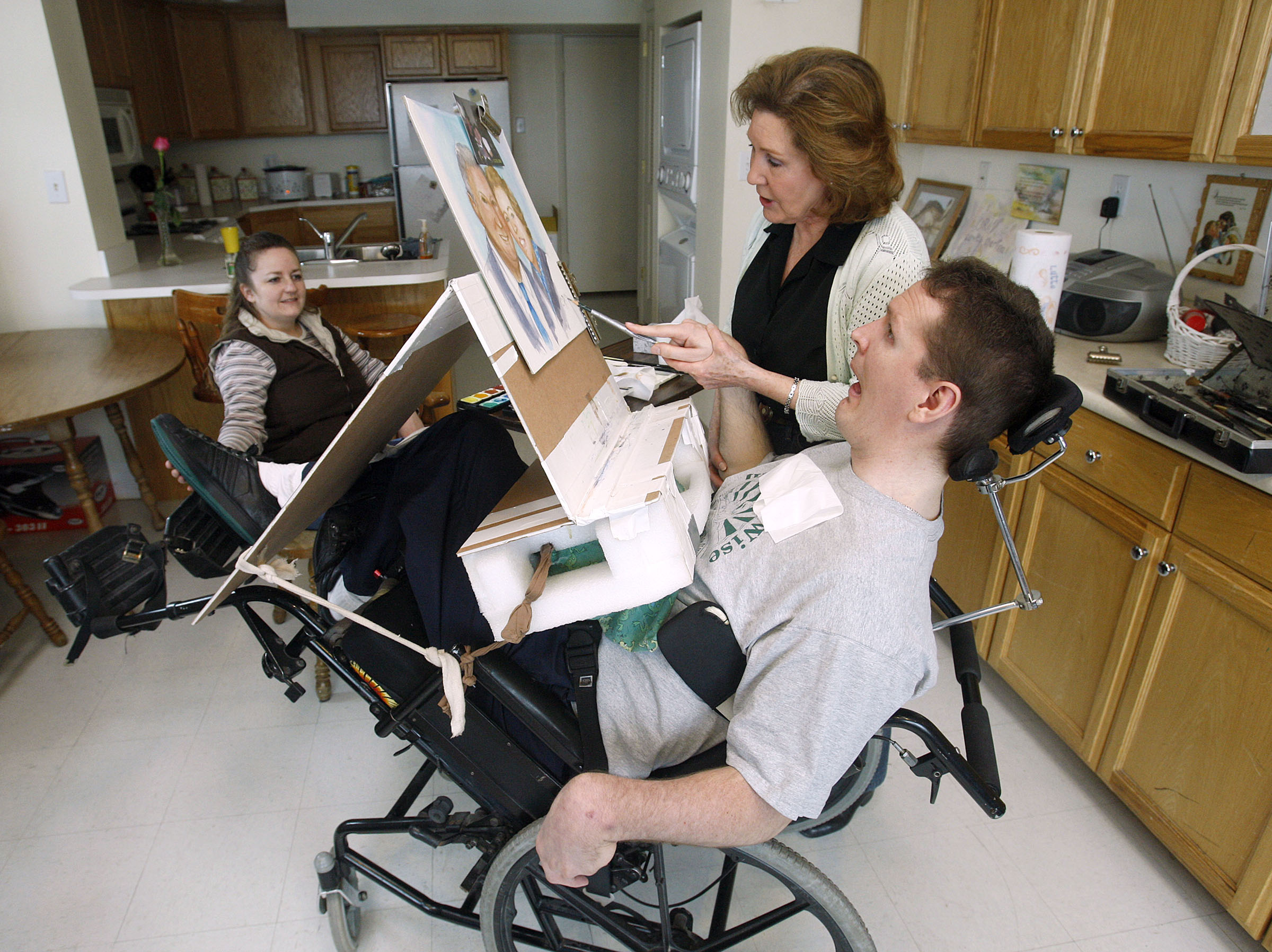 Carol Harding helps Orin Voorheis paint a water color painting of his parents. Harding holds his arm up and shows him where to paint but Voorheis makes the strokes and chooses the colors he wants to use in his paintings. His wife, Chartina Voorheis (at left), watches as he paints.