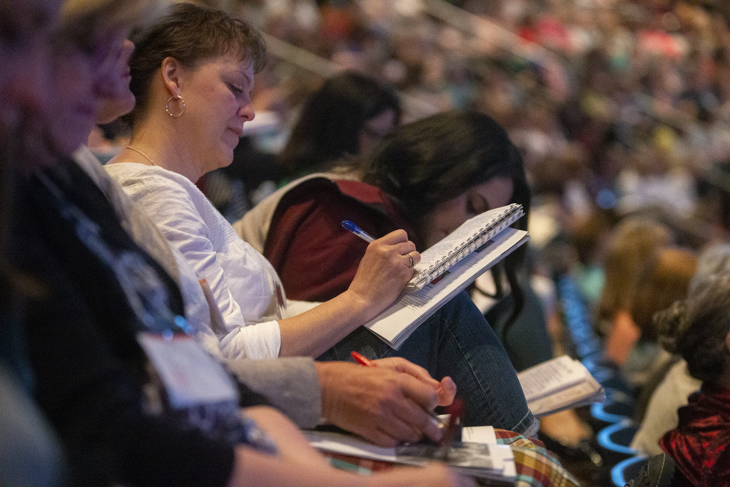 "Women take notes as they attend a ""Sister to Sister"" event at Women's Conference at BYU's Marriott Center in Provo, Utah, on Friday, May 3, 2019."