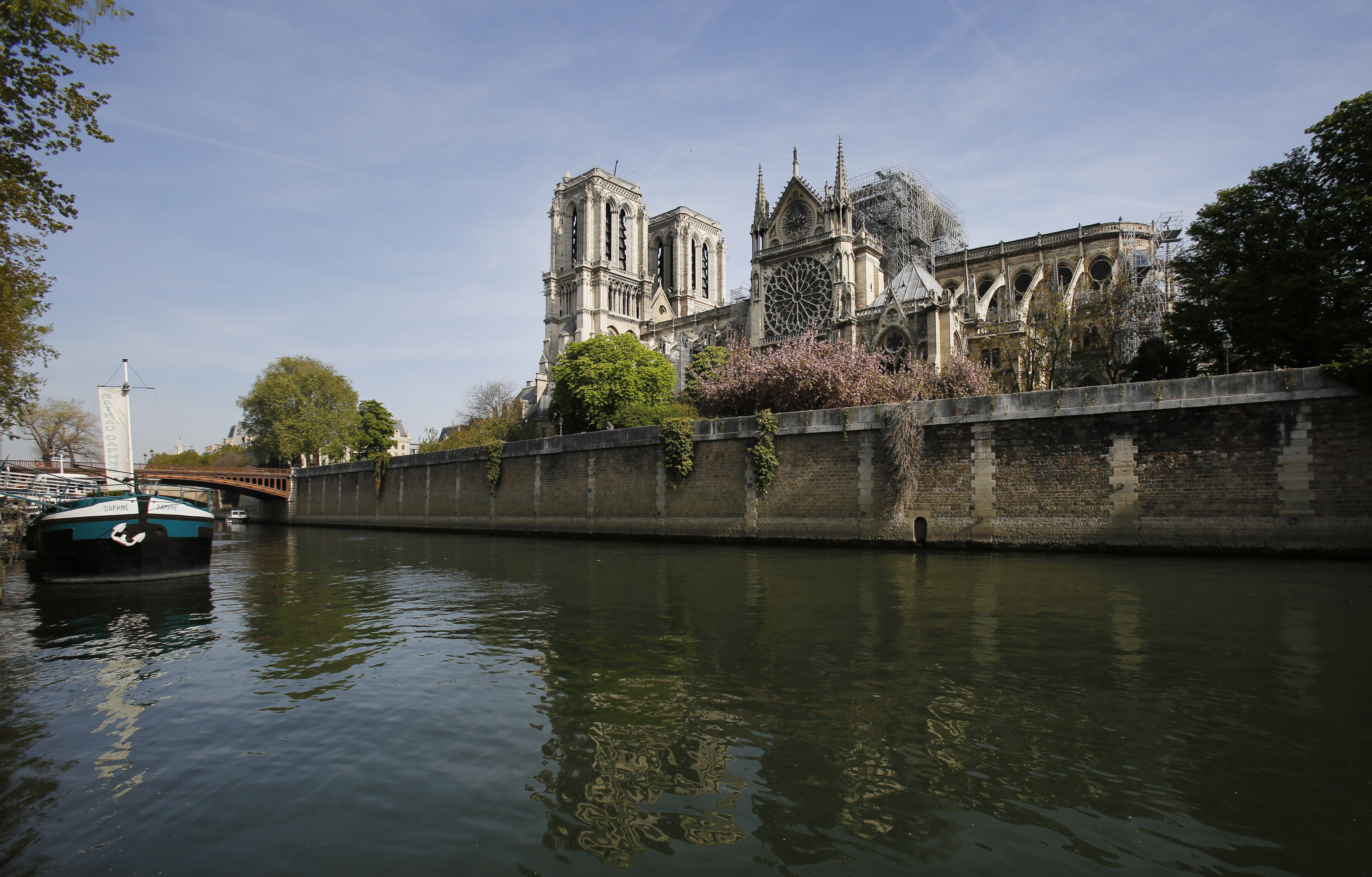 The Seine flows under the Pont Au Double bridge next to the Notre Dame Cathedral in Paris, Thursday, April 18, 2019. Nearly $1 billion has already poured in from ordinary worshippers and high-powered magnates around the world to restore Notre Dame Cathedral in Paris after a massive fire.