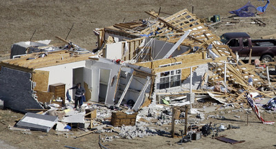 A woman looks through wreckage of home destroyed by a tornado in Lone Grove, Okla., Wednesday, Feb. 11, 2009. Emergency crews on Wednesday searched for more victims amid the wreckage of homes and businesses smashed by a cluster of tornadoes that killed at least eight people.