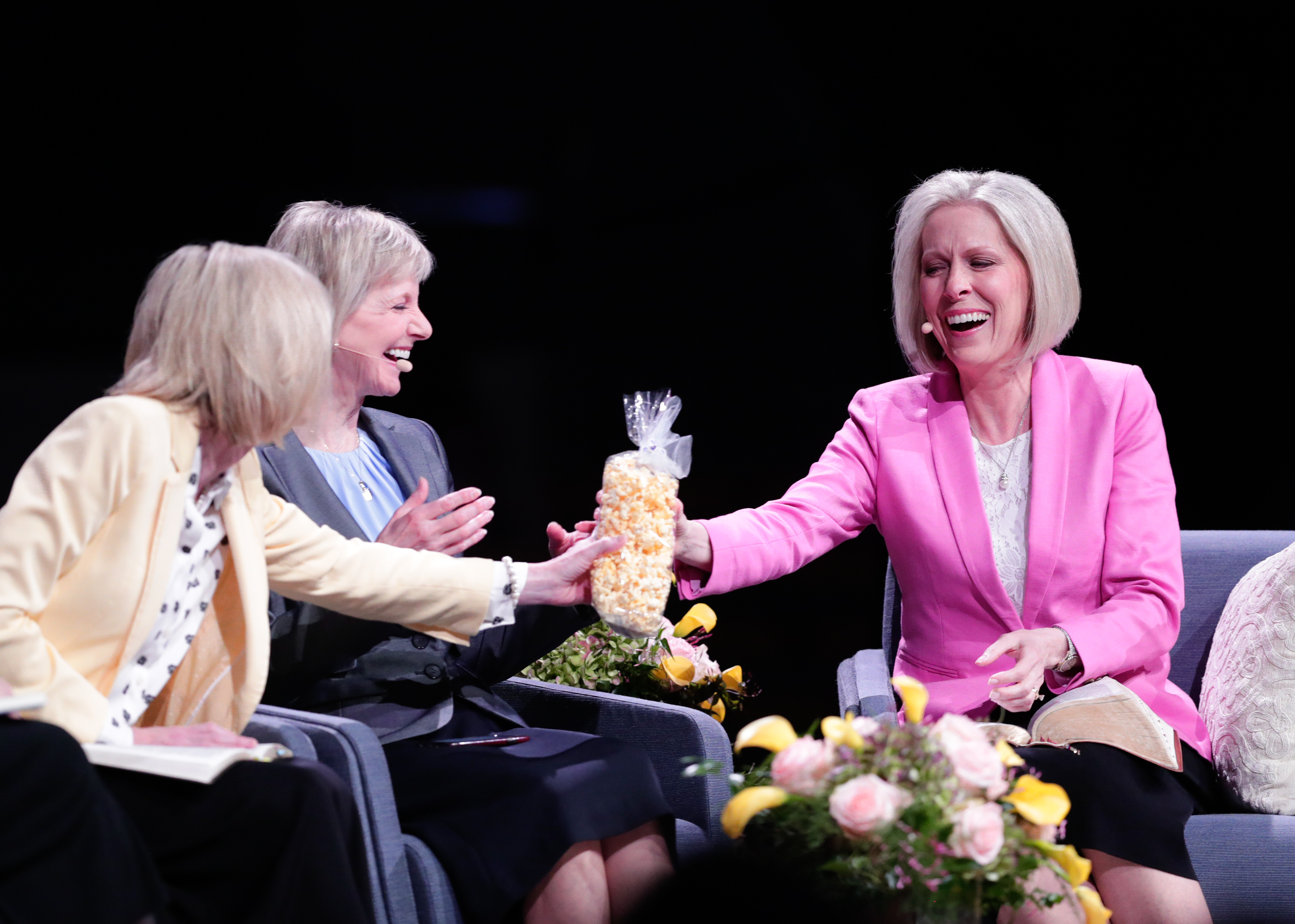 Sister Bonnie H. Cordon gives Sister Joy D. Jones a bag of popcorn during the first Sister-to-Sister event during the 2019 BYU Women's Conference, held in the Marriott Center at BYU in Provo, Utah, on May 3, 2019.